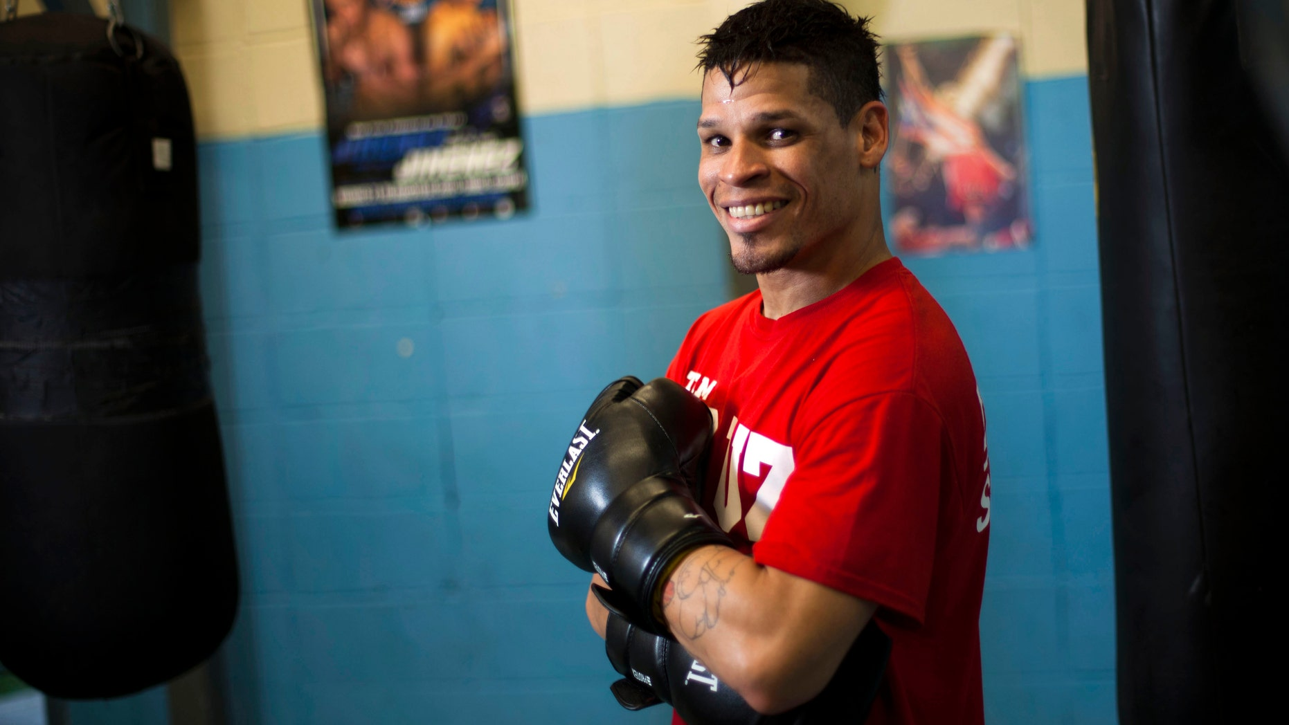 Boxer Orlando Cruz poses for pictures after a training session at a public gym in San Juan, Puerto Rico, Oct. 4, 2012.