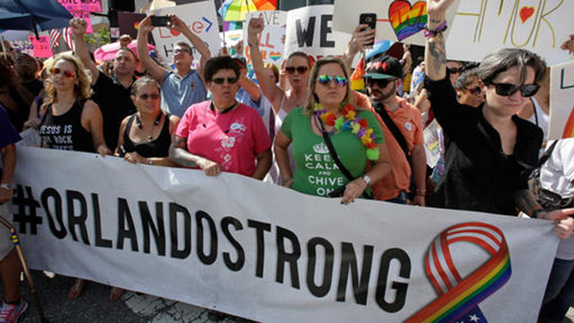 FILE- In this June 18, 2016 file photo, demonstrators show their support during the funeral service for Christopher Andrew Leinonen, one of the victims of the Pulse nightclub mass shooting, outside the Cathedral Church of St. Luke, in Orlando, Fla. Following the attack, other victims of mass shootings reached out to the survivors and their families to ensure that mistakes made with previous charity efforts were not repeated. (AP Photo/John Raoux, File)
