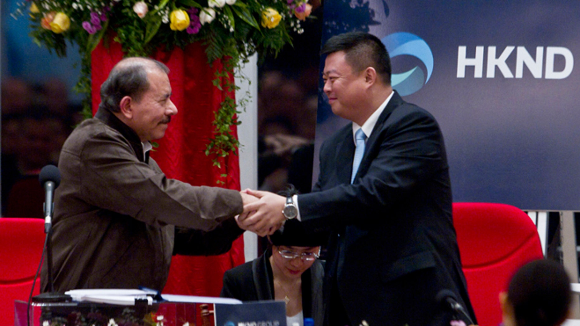 Nicaragua's President Daniel Ortega, left, and Chinese businessman Wang Jing shake hands before signing a concession agreement for the construction of a multibillion-dollar canal at the Casa de los Pueblos in Managua, Nicaragua, Friday, June 14, 2013.  Legislation approved by a 61-25 vote in the National Assembly dominated by Ortega's Sandinista Front contains no specific route for the canal and virtually no details of its financing or economic viability, but it grants a Hong Kong-based company 50 years of exclusive rights to study the plan and build and operate a canal in exchange for Nicaragua receiving a minority share of any profits. (AP Photo/Esteban Felix)