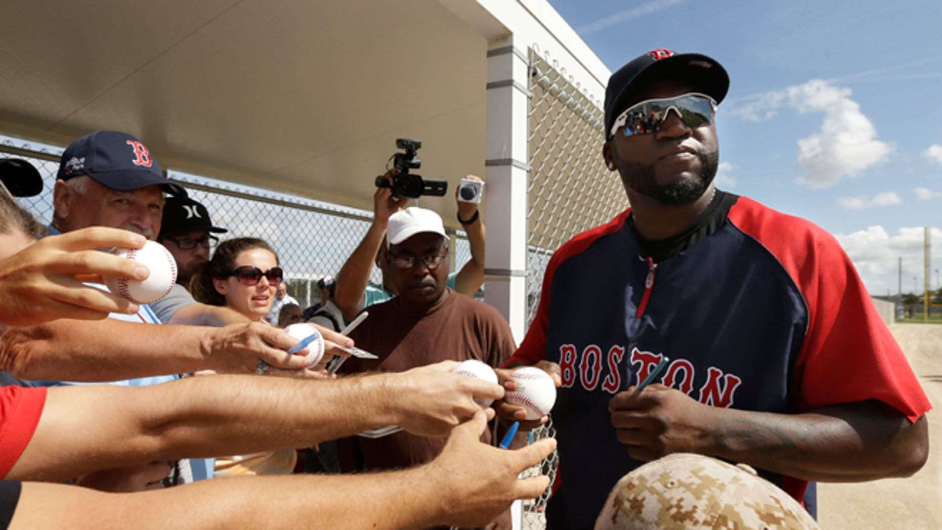 Boston Red Sox designated hitter David Ortiz signs autographs during spring training baseball practice, Sunday, Feb. 23, 2014, in Fort Myers, Fla. (AP Photo/Steven Senne)