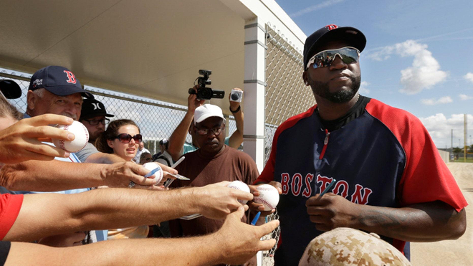 Boston Red Sox designated hitter David Ortiz signs autographs during spring training baseball practice, Sunday, Feb. 23, 2014, in Fort Myers, Fla. (AP Photo/Steven Senne)