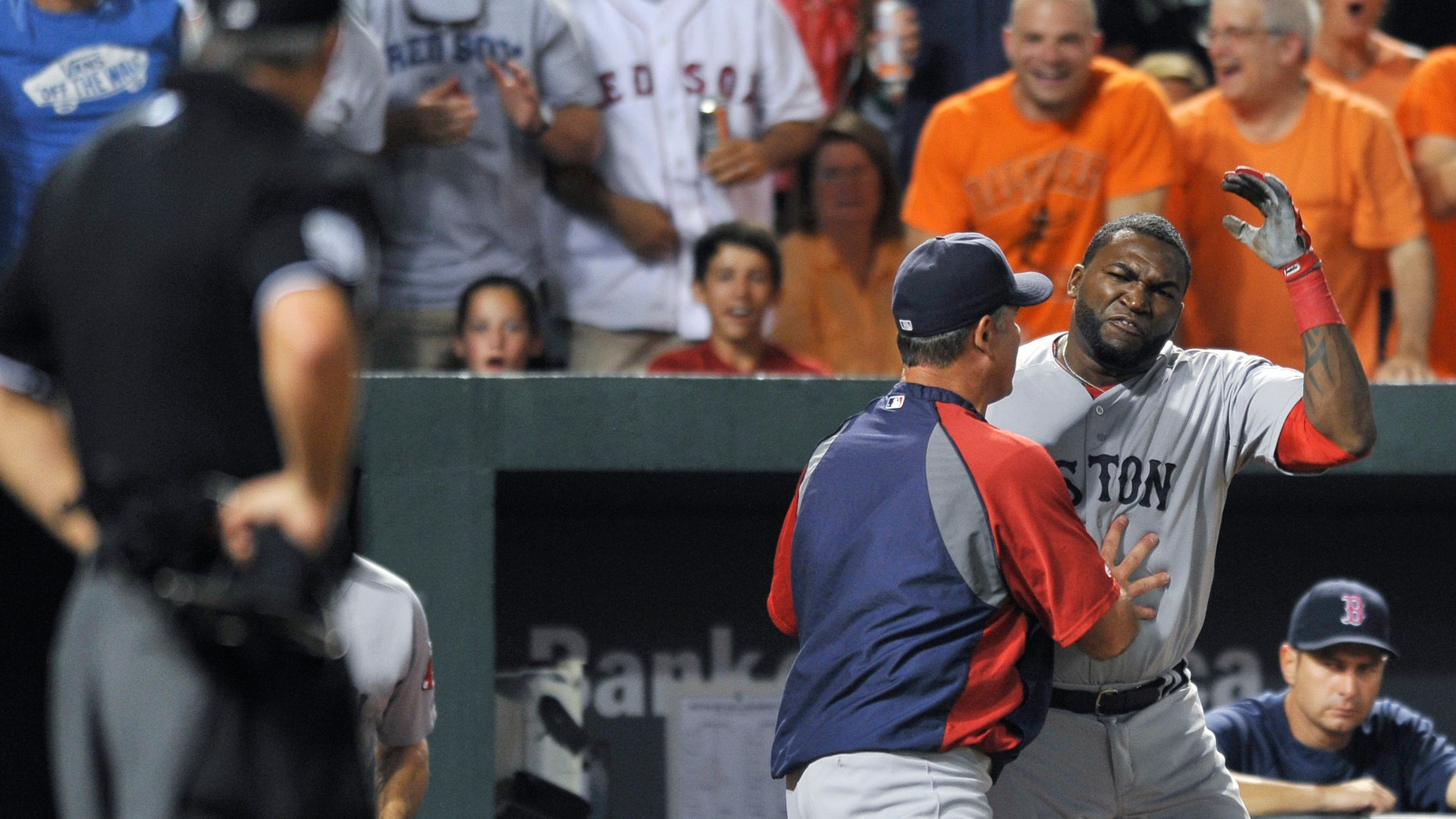 Boston Red Sox designated hitter David Ortiz reacts and is held back by manager John Farrell after being ejected by home plate umpire Tim Timmons for arguing a called third strike in the seventh inning of a baseball game against the Baltimore Orioles, Saturday, July 27, 2013, in Baltimore. Boston won 7-3. (AP Photo/Gail Burton)