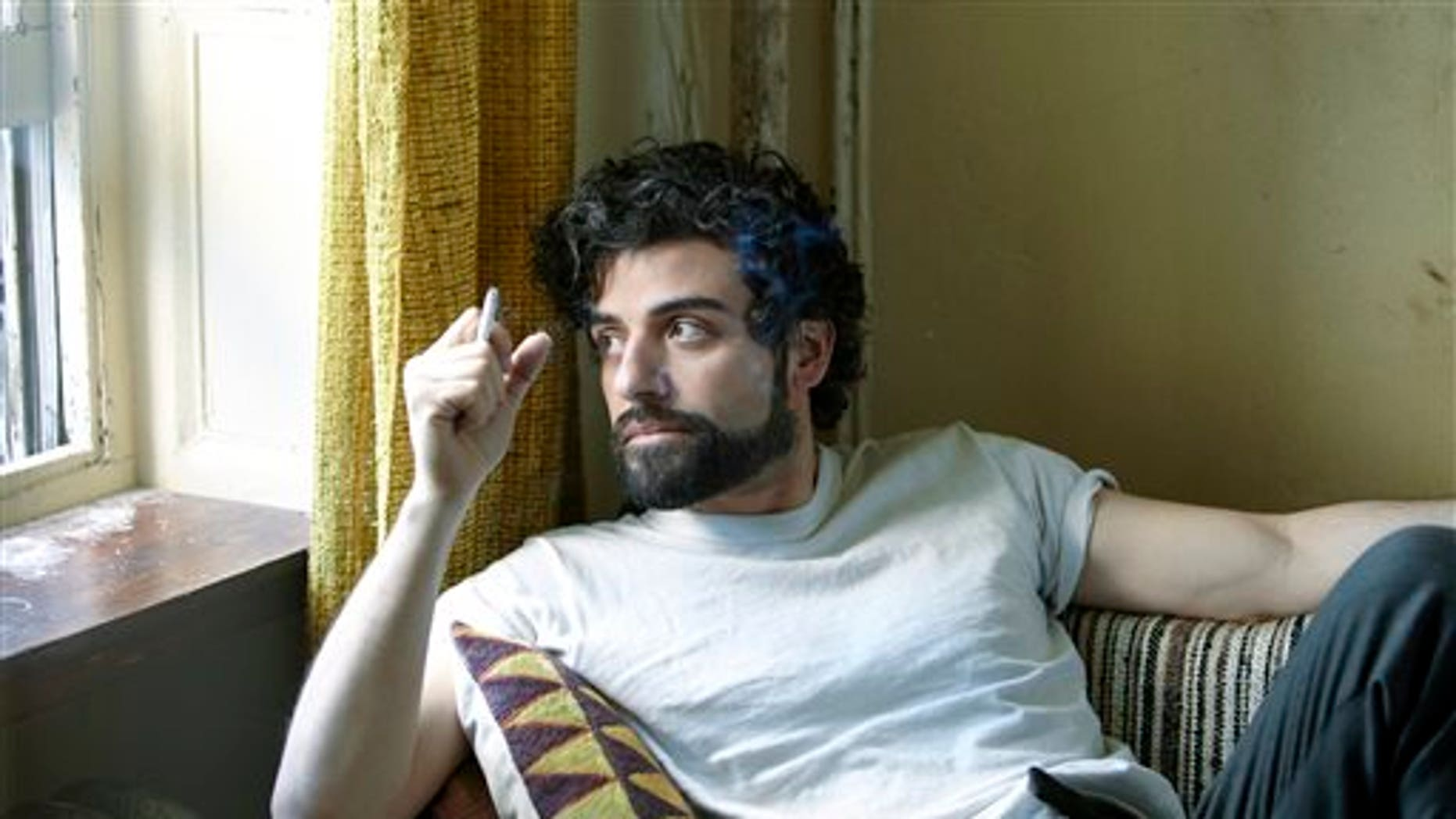 """This film image released by CBS FIlms shows Oscar Isaac in a scene from """"Inside Llewyn Davis."""" Isaac was nominated for a Golden Globe for best actor in a motion picture musical or comedy for his role in the film on Thursday, Dec. 12, 2013.  The 71st annual Golden Globes will air on Sunday, Jan. 12. (AP Photo/CBS FIlms, Alison Rosa)"""
