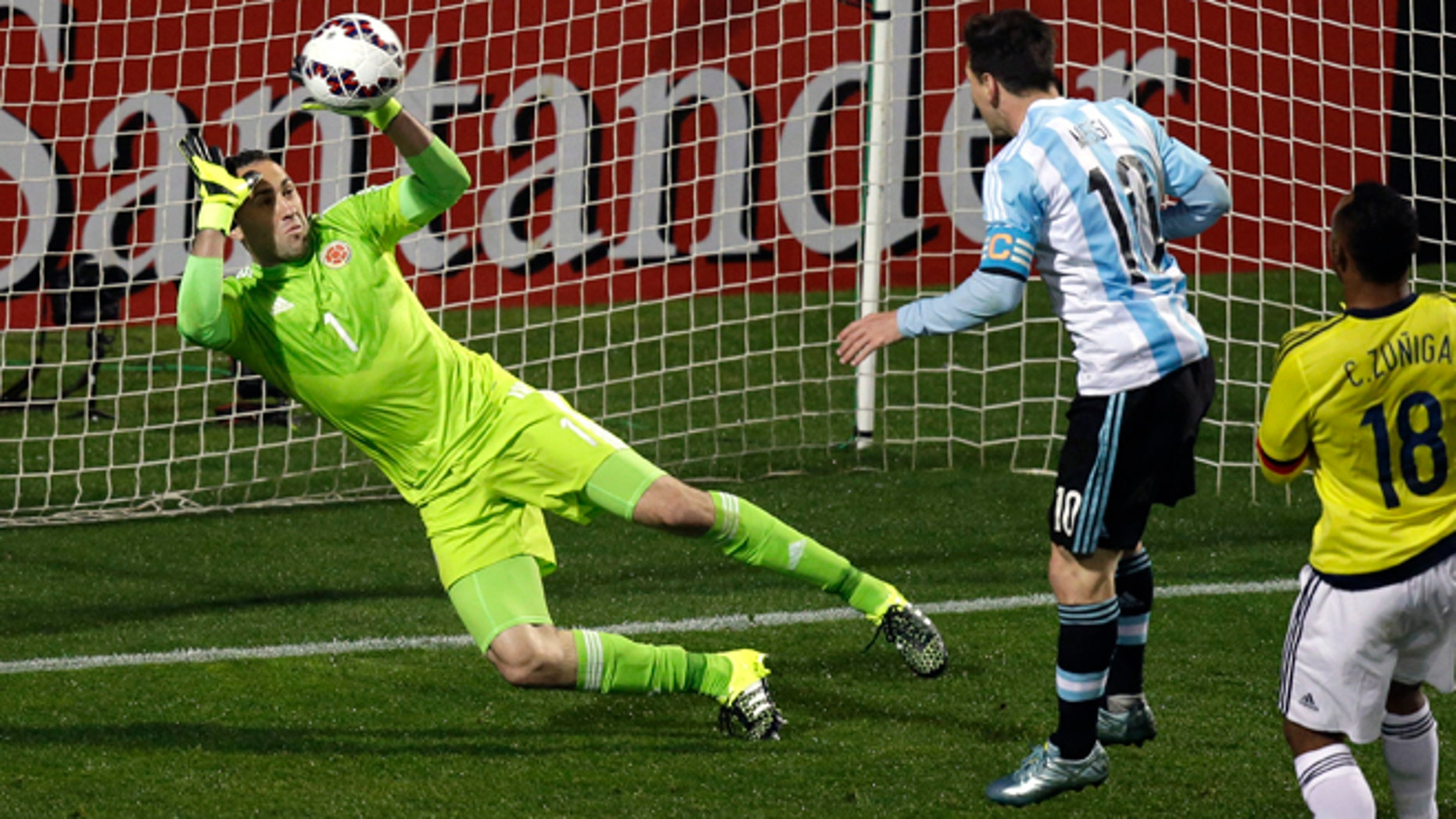 Colombia goalkeeper David Ospina stops a headshot by Argentina's Lionel Messi, center, during a Copa America quarterfinal soccer match at the Sausalito Stadium in Vina del Mar, Chile, Friday, June 26, 2015. (AP Photo/Jorge Saenz)
