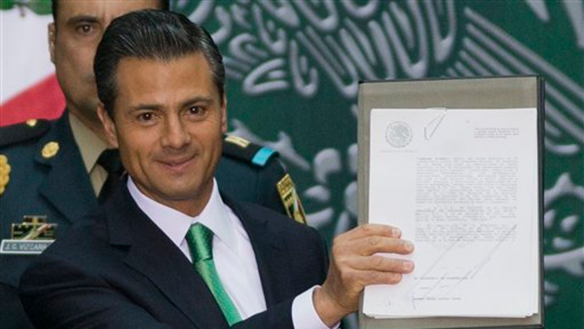Mexico's President Enrique Pena Nieto holds up the documents he signed to enact his proposed energy reforms at the National Palace in Mexico City, Friday, Dec. 20, 2013. The sweeping reforms approved by state legislators allow private companies to explore for and produce oil and gas, capping a remarkable series of legislative victories by the Mexican leader. (AP Photo/Eduardo Verdugo)
