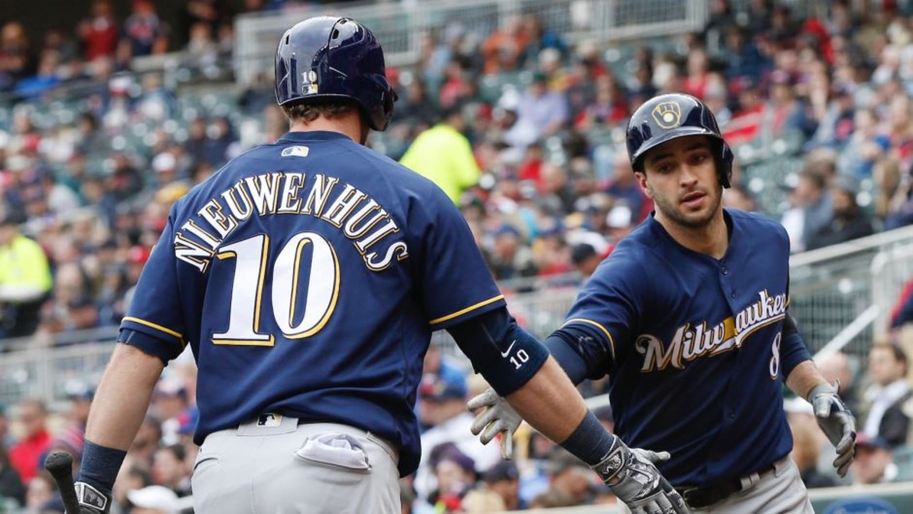 Milwaukee Brewers' Ryan Braun, right, is congratulated by Kirk Nieuwenhuis after scoring on a sacrifice fly by Chris Carter off Minnesota Twins pitcher Ervin Santana, right, in the fifth inning of a baseball game Tuesday, April 19, 2016, in Minneapolis. (AP Photo/Jim Mone)