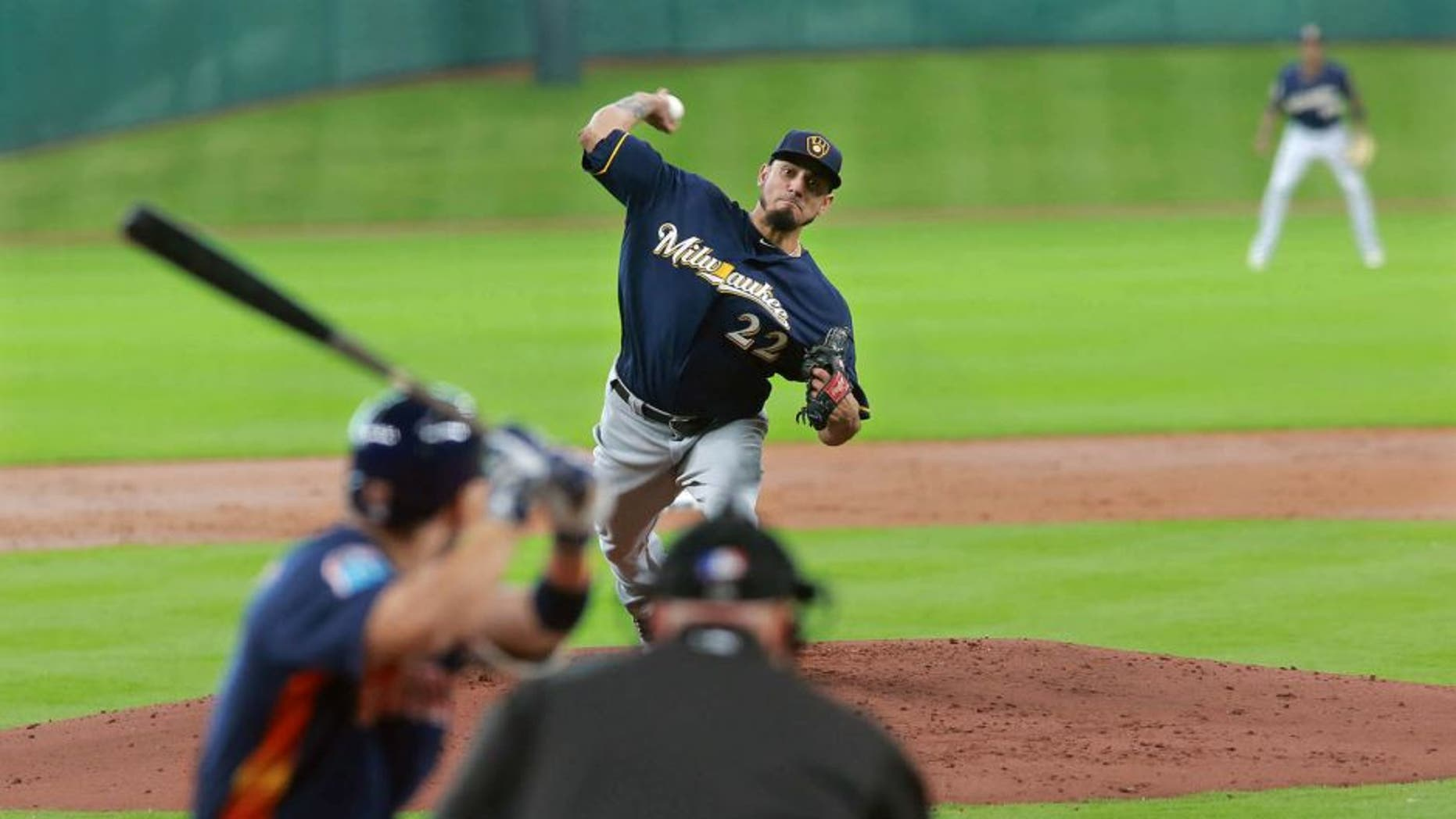 Milwaukee Brewers pitcher Matt Garza delivers a pitch to Houston Astro' Jose Altuve in the first inning of an exhibition baseball game Friday, April 1, 2016 in Houston. (AP Photo/Richard Carson)