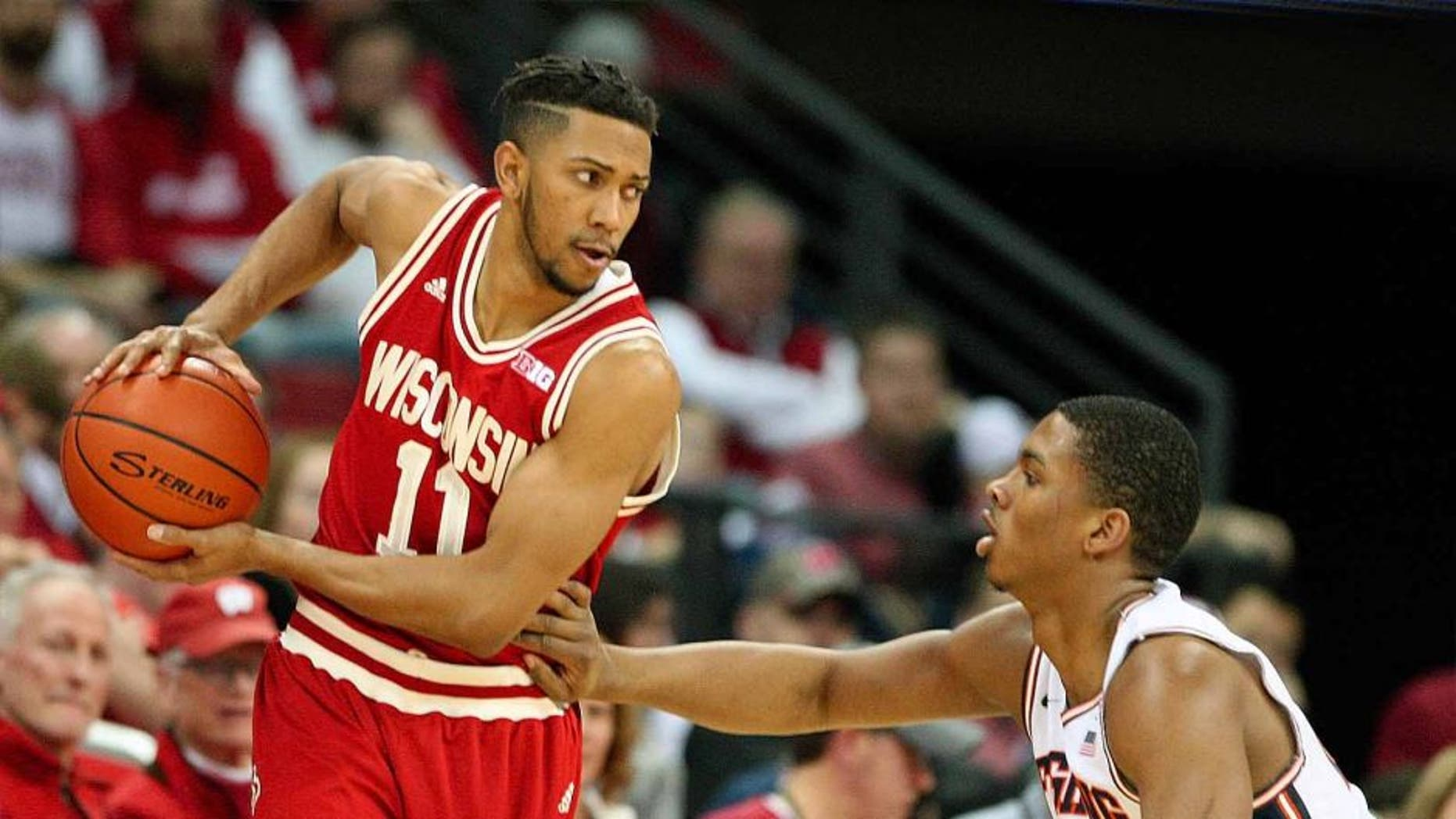 Wisconsin Badgers guard Jordan Hill looks to pass as Illinois guard Malcolm Hill defends during the first half at the Kohl Center in Madison, Wis., on Sunday, Feb. 21, 2016.