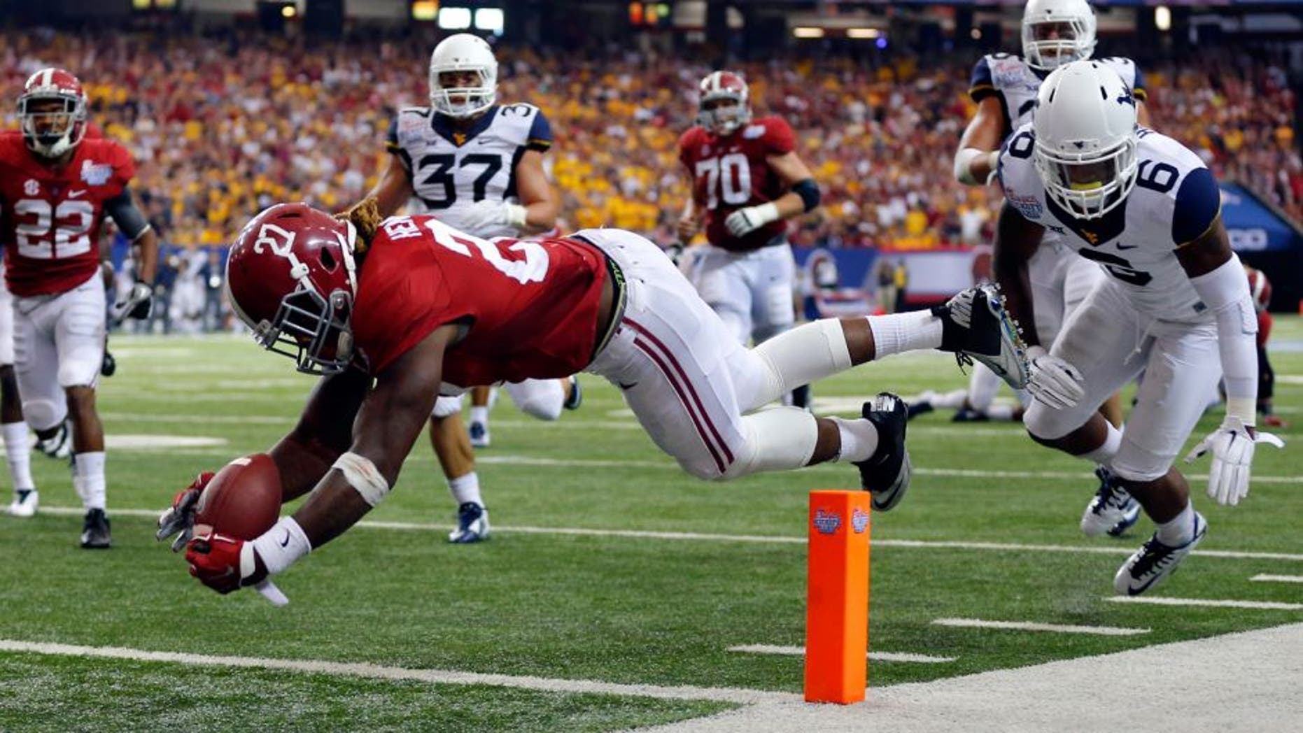 Aug 30, 2014; Atlanta, GA, USA; Alabama Crimson Tide running back Derrick Henry (27) dives for a touchdown against West Virginia Mountaineers cornerback Dravon Henry (6) during the third quarter of the 2014 Chick-fil-a kickoff game at Georgia Dome. Mandatory Credit: Paul Abell-USA TODAY Sports