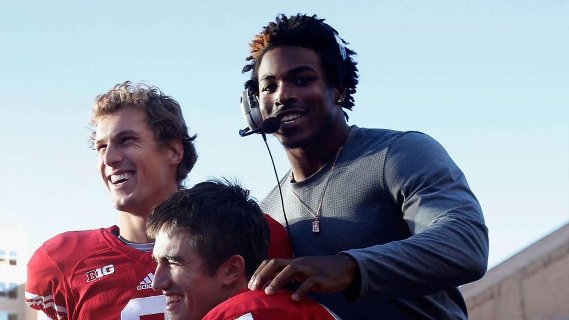 Corey Clement (top right) celebrates with quarterback Joel Stave (left) and Andrew Endicott during the final moments of a 28-3 win against the Troy Trojans at Camp Randall Stadium on September 19, 2015, in Madison, Wisconsin.