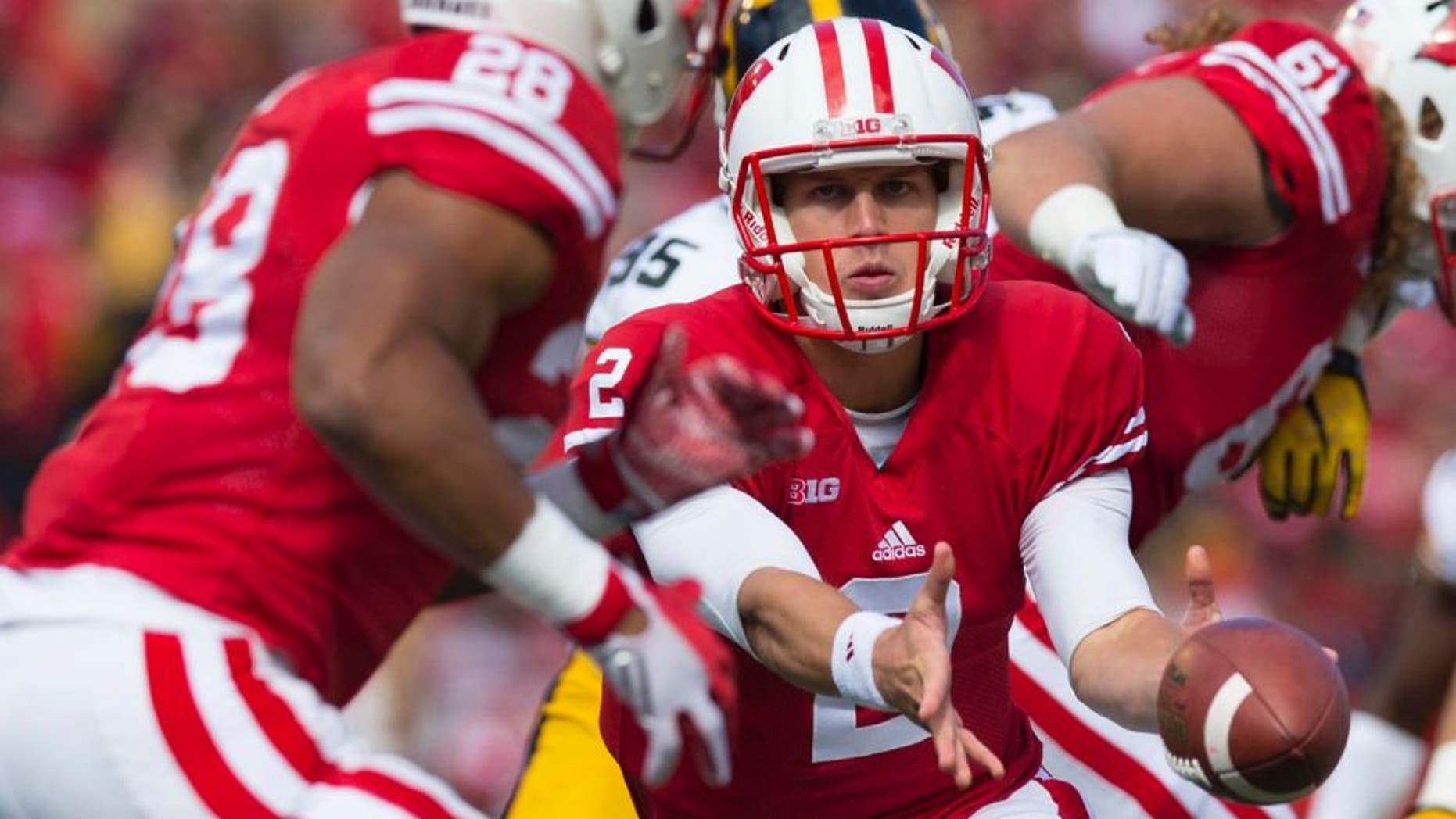 Wisconsin Badgers quarterback Joel Stave pitches the football to running back Taiwan Deal during the first quarter against the Iowa Hawkeyes at Camp Randall Stadium in Madison, Wis., on Saturday, Oct. 3, 2015.