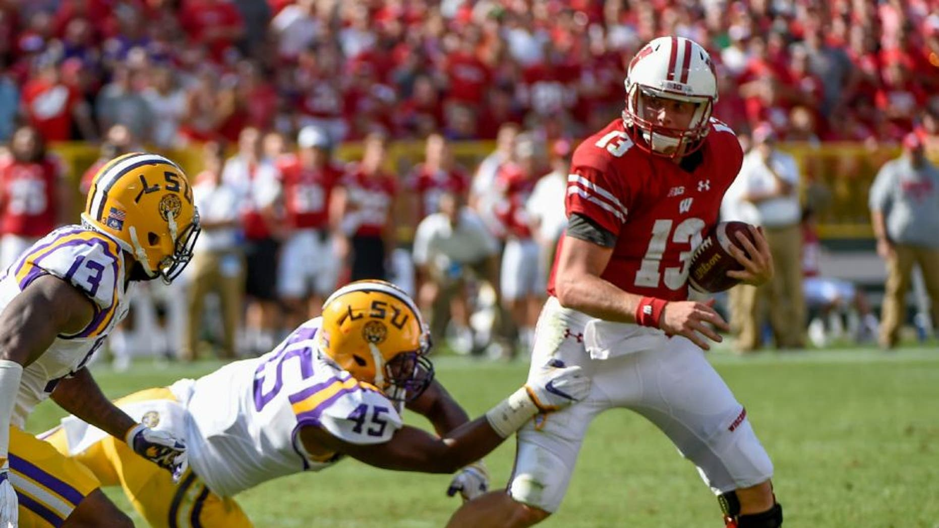 Wisconsin Badgers quarterback Bart Houston (right) tries to break a tackle by LSU Tigers linebacker Michael Divinity Jr., left in the 2nd quarter at Lambeau Field.
