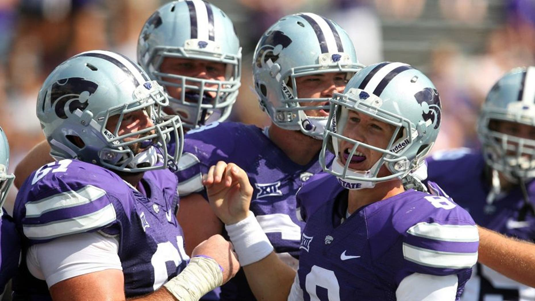 Sep 27, 2014; Manhattan, KS, USA; Kansas State Wildcats quarterback Joe Hubener (8) is congratulated by teammates following a touchdown in a 58-28 win against the UTEP Miners at Bill Snyder Family Stadium. Mandatory Credit: Scott Sewell-USA TODAY Sports