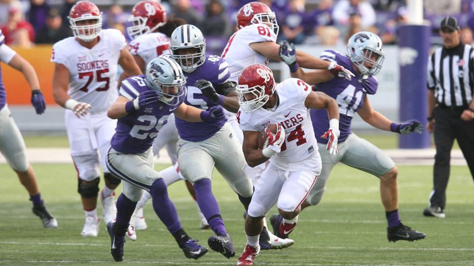 Oct 17, 2015; Manhattan, KS, USA; Oklahoma Sooners running back Daniel Brooks (34) is chased by Kansas State Wildcats defensive back Sean Newlan (29) during the Sooners 55-0 win at Bill Snyder Family Football Stadium. Mandatory Credit: Scott Sewell-USA TODAY Sports