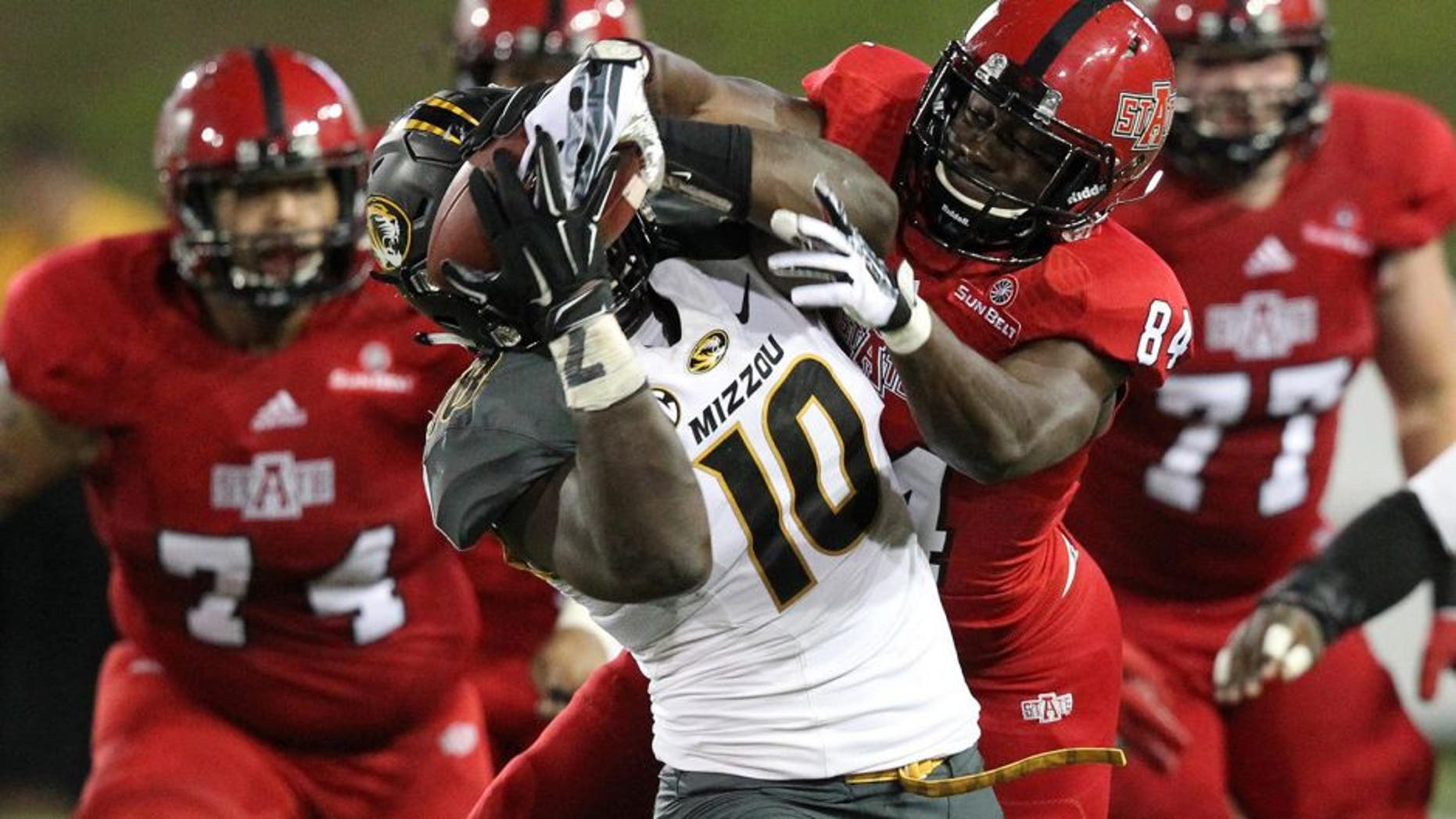 Sep 12, 2015; Jonesboro, AR, USA; Arkansas State Red Wolves wide receiver Dijon Pachal (84) fights for the ball as Missouri Tigers linebacker Kentrell Brothers (10) strips it for an interception in the fourth quarter at ASU Stadium. Missouri defeated Arkansas State 27-20. Mandatory Credit: Nelson Chenault-USA TODAY Sports