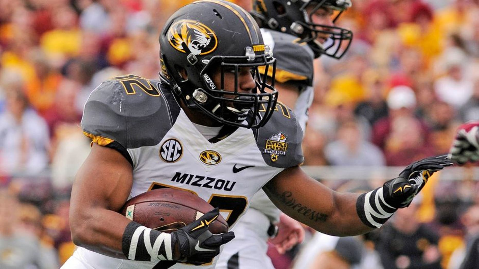 Jan 1, 2015; Orlando, FL, USA; Missouri Tigers running back Russell Hansbrough (32) runs the ball against the Minnesota Golden Gophers in the first quarter of the 2015 Citrus Bowl at Florida Citrus Bowl. Mandatory Credit: David Manning-USA TODAY Sports