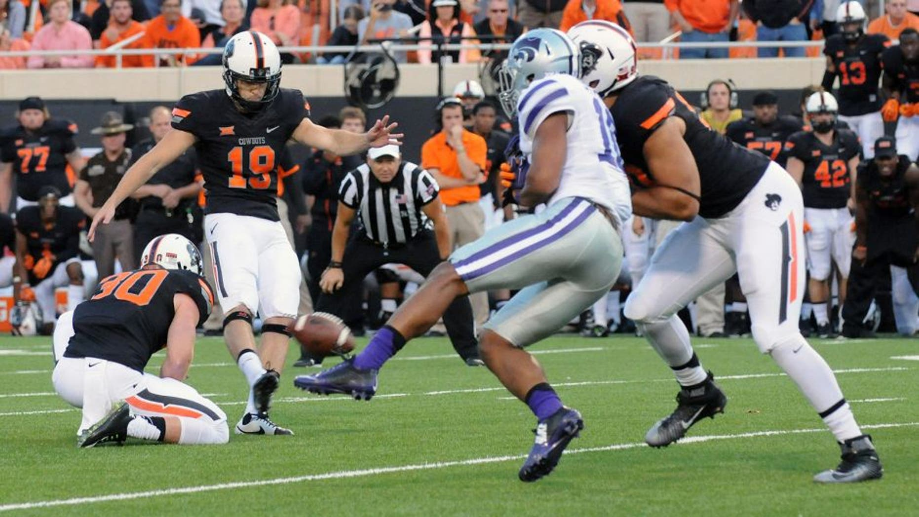 Oklahoma State defensive end Trace Clark, right, defends against Kansas State defensive back Donnie Starks, center right, while Oklahoma State kicker Ben Grogan, center left, kicks the winning field goal held by Oklahoma State holder Bryant Reber, left, during the final seconds of an NCAA football game in Stillwater, Okla., Saturday, Oct. 3, 2015. (AP Photo/Brody Schmidt)