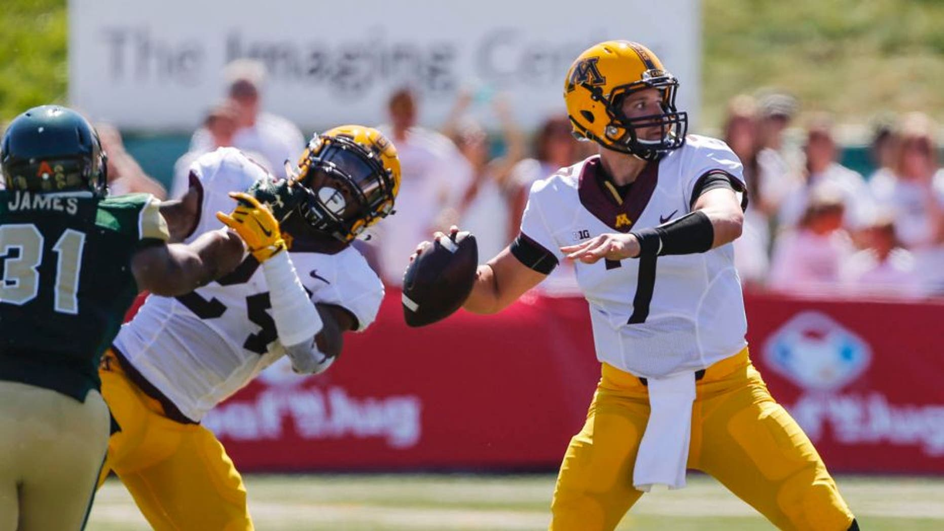 Minnesota Golden Gophers quarterback Mitch Leidner is protected by teammate Rodney Smith against Colorado State Rams linebacker Cory James during the first quarter at Sonny Lubick Field at Hughes Stadium in Fort Collins, Colo., on Sunday, Sept. 12, 2015.