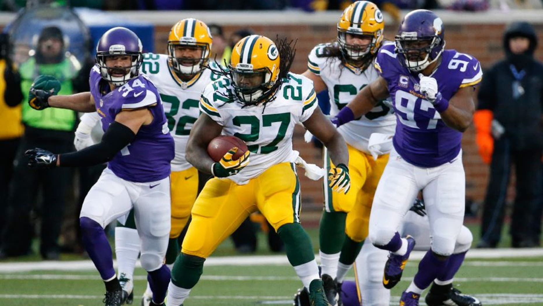 Green Bay Packers running back Eddie Lacy (27) runs past Minnesota Vikings strong safety Andrew Sendejo (34) an defensive end Everson Griffen (97) during the first half of an NFL football game in Minneapolis, Sunday, Nov. 22, 2015.