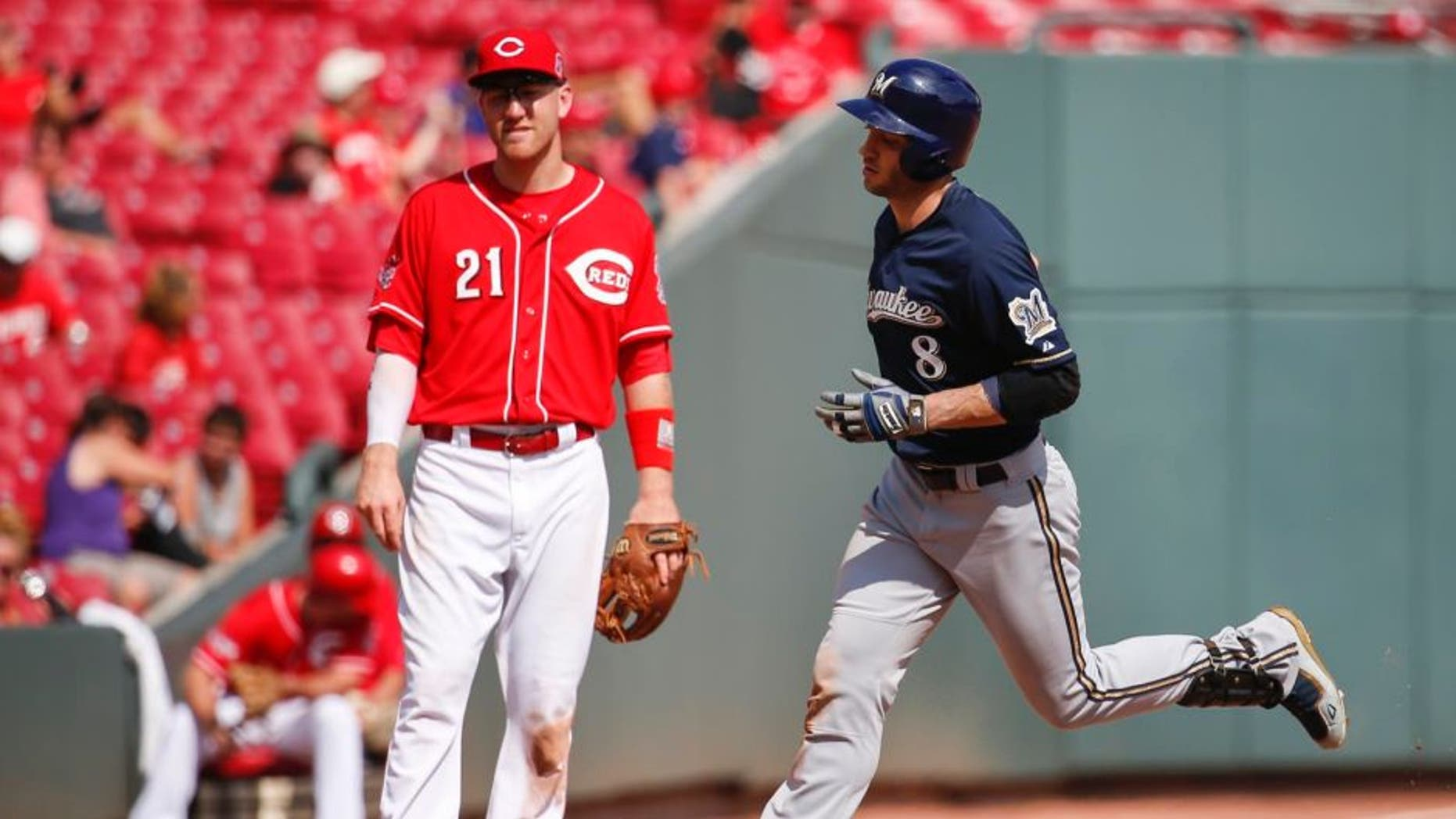 The Milwaukee Brewers' Ryan Braun rounds third after hitting a solo home run as Cincinnati Reds third baseman Todd Frazier looks on in the eighth inning Sunday, Sept. 6, 2015, in Cincinnati.