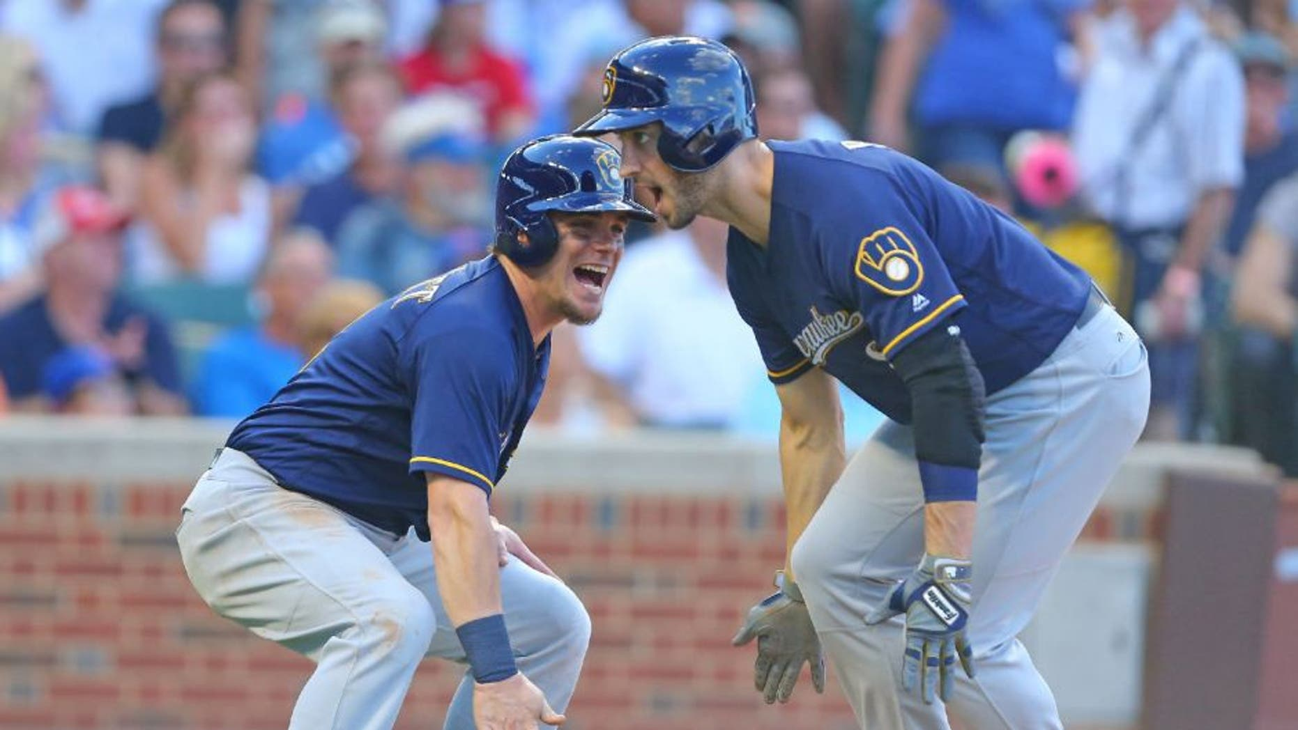 Milwaukee Brewers left fielder Ryan Braun celebrates his two RBI home run with second baseman Scooter Gennett during the sixth inning against the Chicago Cubs.
