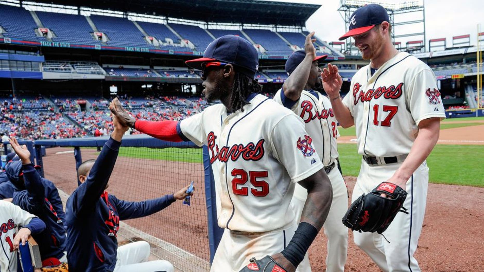 Atlanta Braves center fielder Cameron Maybin (25) is followed by pitcher Shelby Miller (17) as he is congratulated while entering the dugout after catching a fly ball hit by St. Louis Cardinals' Brandon Moss and throwing out Greg Garcia at first to turn a double play during the fourth inning of the first baseball game of a doubleheader, Sunday, Oct. 4, 2015, in Atlanta. (AP Photo/John Amis)