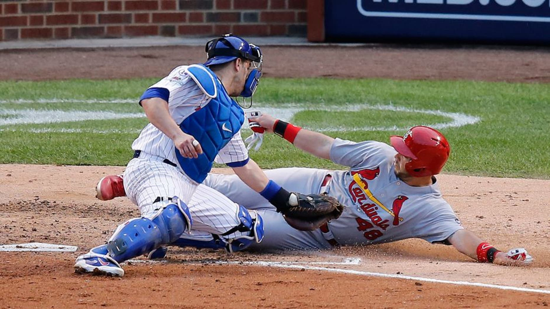 Chicago Cubs catcher Miguel Montero (47) tags out St. Louis Cardinals' Tony Cruz (48) during the sixth inning of Game 4 in baseball's National League Division Series, Tuesday, Oct. 13, 2015, in Chicago. (AP Photo/Charles Rex Arbogast)