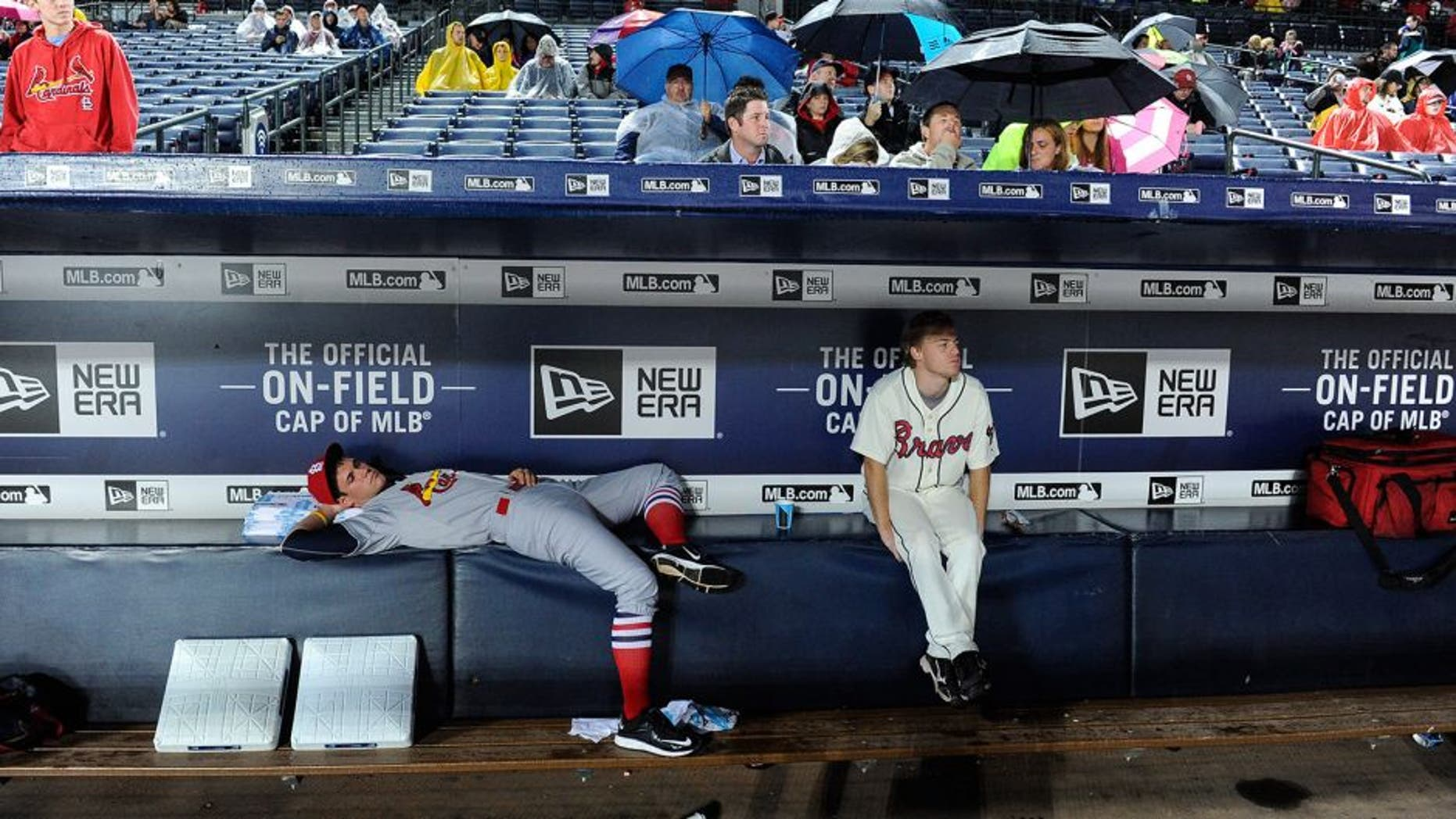 Bat boys wait out a weather-delayed start to the Atlanta Braves against the St. Louis Cardinals baseball game, Saturday, Oct. 3, 2015, in Atlanta. (AP Photo/John Amis)