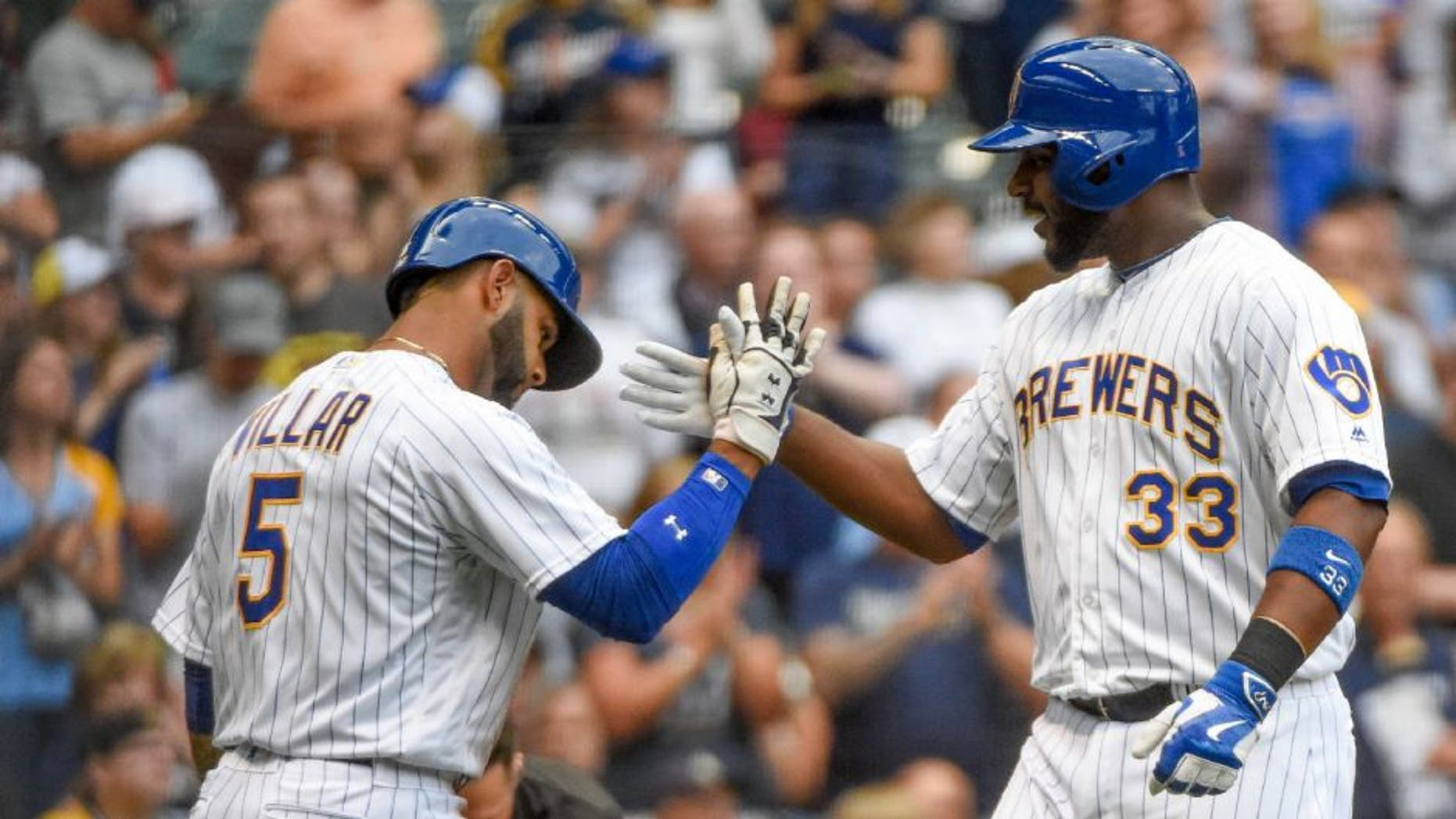 Milwaukee Brewers first baseman Chris Carter, right, is greeted by Jonathan Villar after hitting a two-run home run during the first inning against the Pittsburgh Pirates on Friday, July 29.