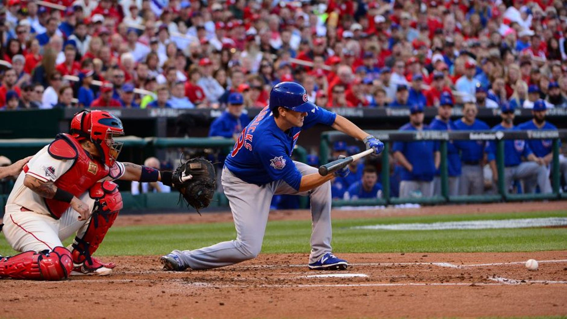 Oct 10, 2015; St. Louis, MO, USA; Chicago Cubs starting pitcher Kyle Hendricks (right) hits a sacrifice bunt against St. Louis Cardinals catcher Yadier Molina (left) scoring Cubs left fielder Austin Jackson (not pictured) during the second inning in game two of the NLDS at Busch Stadium. Mandatory Credit: Jeff Curry-USA TODAY Sports