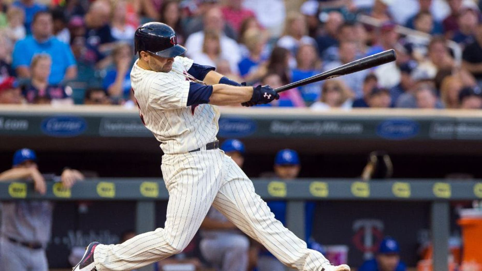 Minnesota Twins second baseman Brian Dozier hits his 100th career home run in the sixth inning against the Kansas City Royals on Saturday, Aug. 12, 2016, in Minneapolis.