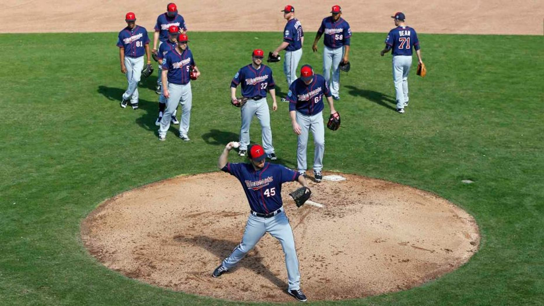 Minnesota Twins pitcher Phil Hughes runs a drill as teammates watch during a spring training baseball workout in Fort Myers, Fla., Monday, Feb. 22, 2016.