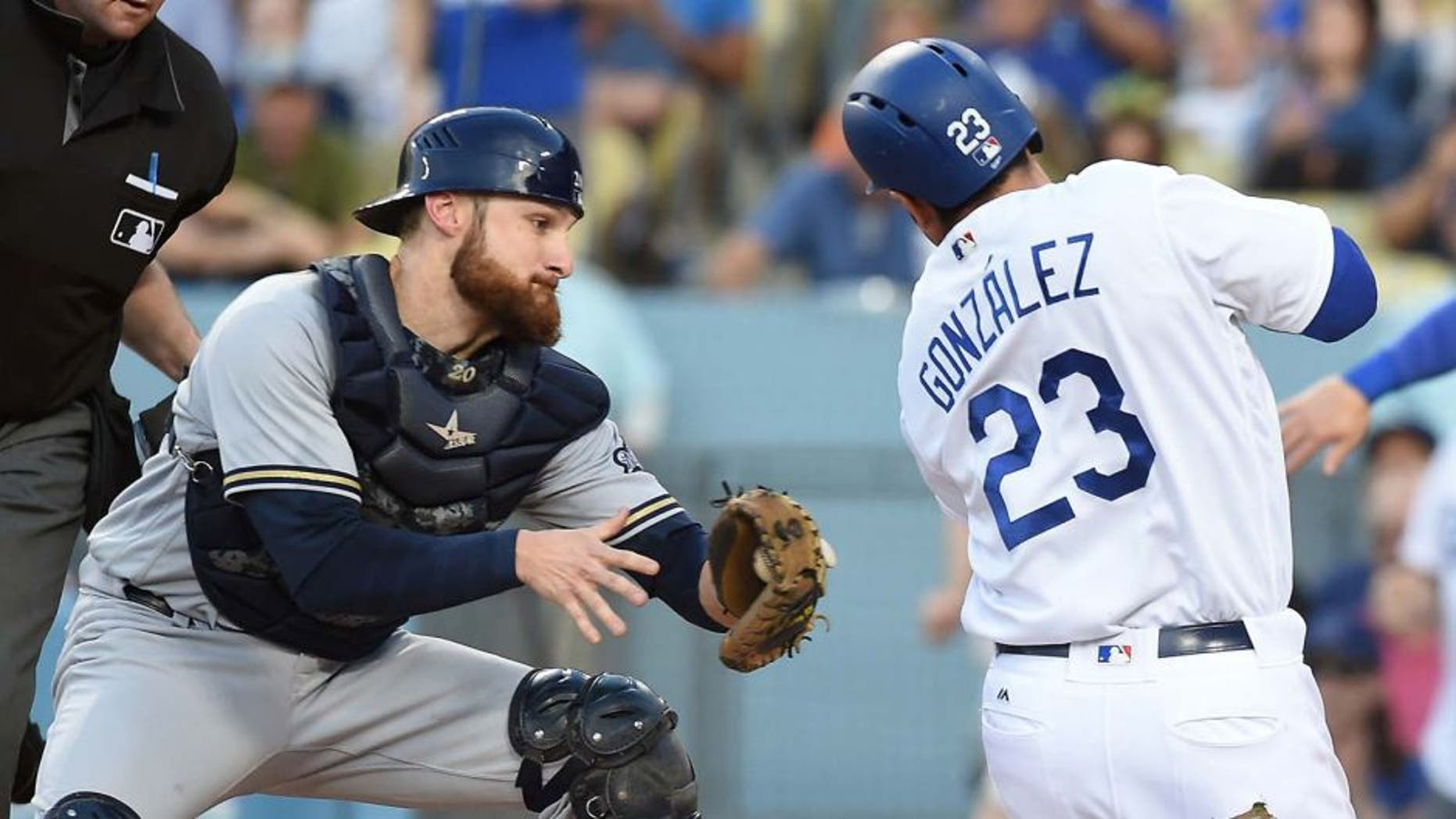 Milwaukee Brewers catcher Jonathan Lucroy tags out Los Angeles Dodgers first baseman Adrian Gonzalez in the second inning at Dodger Stadium in Los Angeles on June 18, 2016.