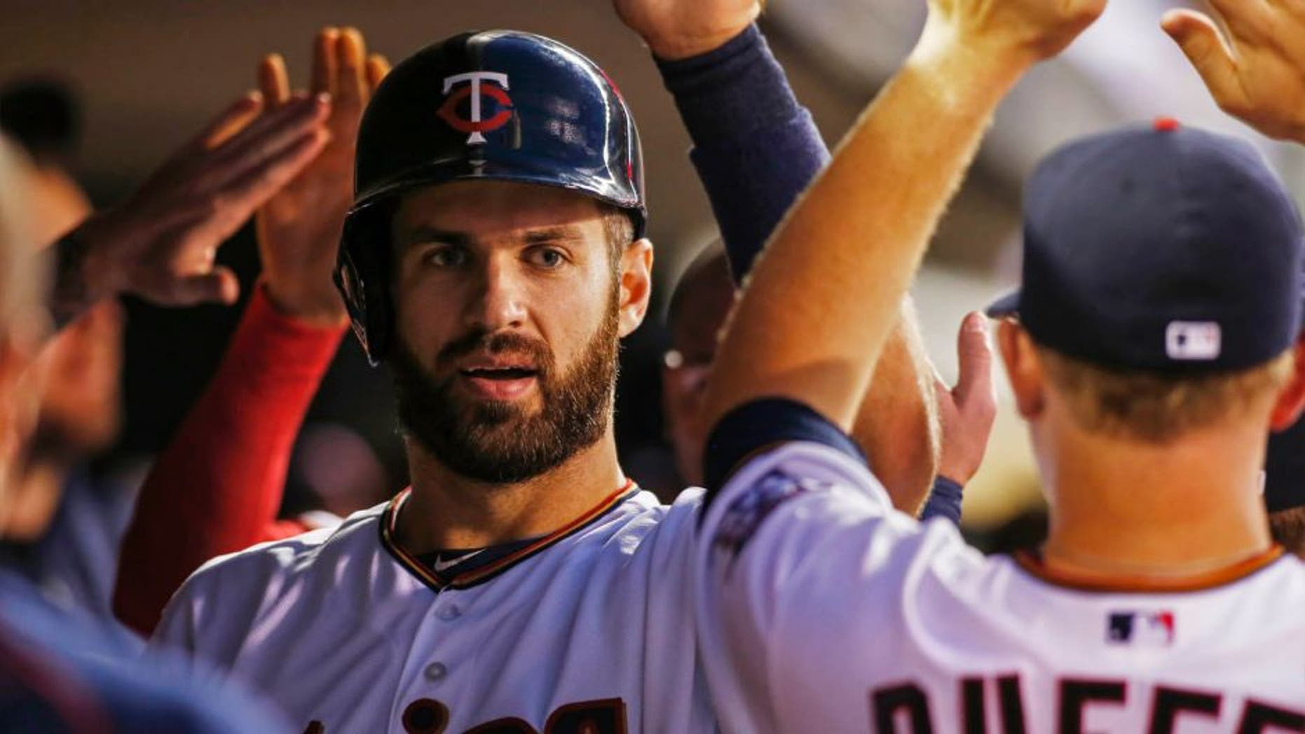 Minnesota Twins first baseman Joe Mauer celebrates his run against the Detroit Tigers in the first inning of a baseball game, Monday, Sept. 14, 2015, in Minneapolis.