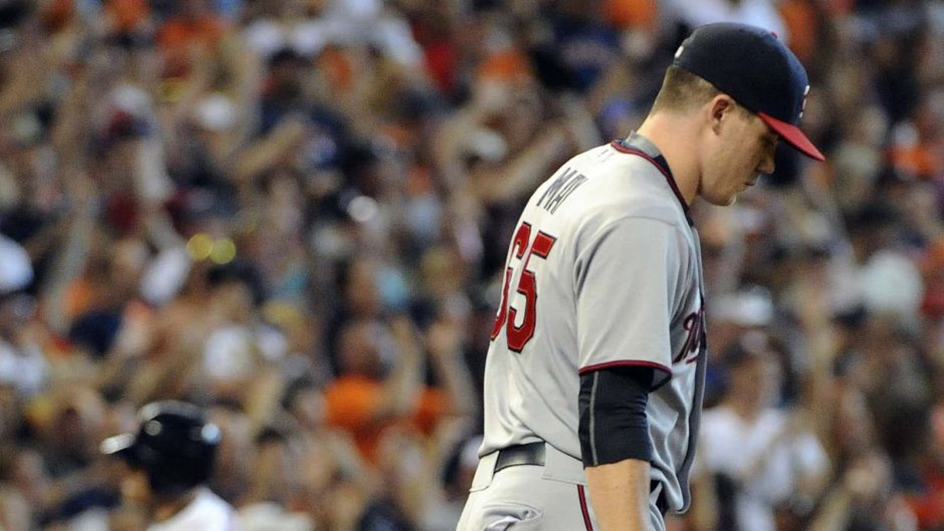 Minnesota Twins relief pitcher Trevor May walks back to the mound as Jed Lowrie rounds third base after hitting a grand slam in the seventh inning Sunday, Sept. 6, 2015, in Houston.