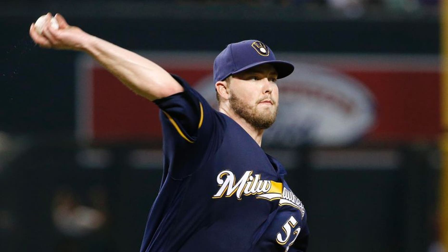 The Milwaukee Brewers' Jimmy Nelson makes a pickoff throw during the fourth inning against the Arizona Diamondbacks on Sunday, Aug. 7, 2016, in Phoenix. The throw sailed over the head of first baseman Andy Wilkins and Diamondbacks runners Jean Segura advanced to third base and Paul Goldschmidt advanced to second base.