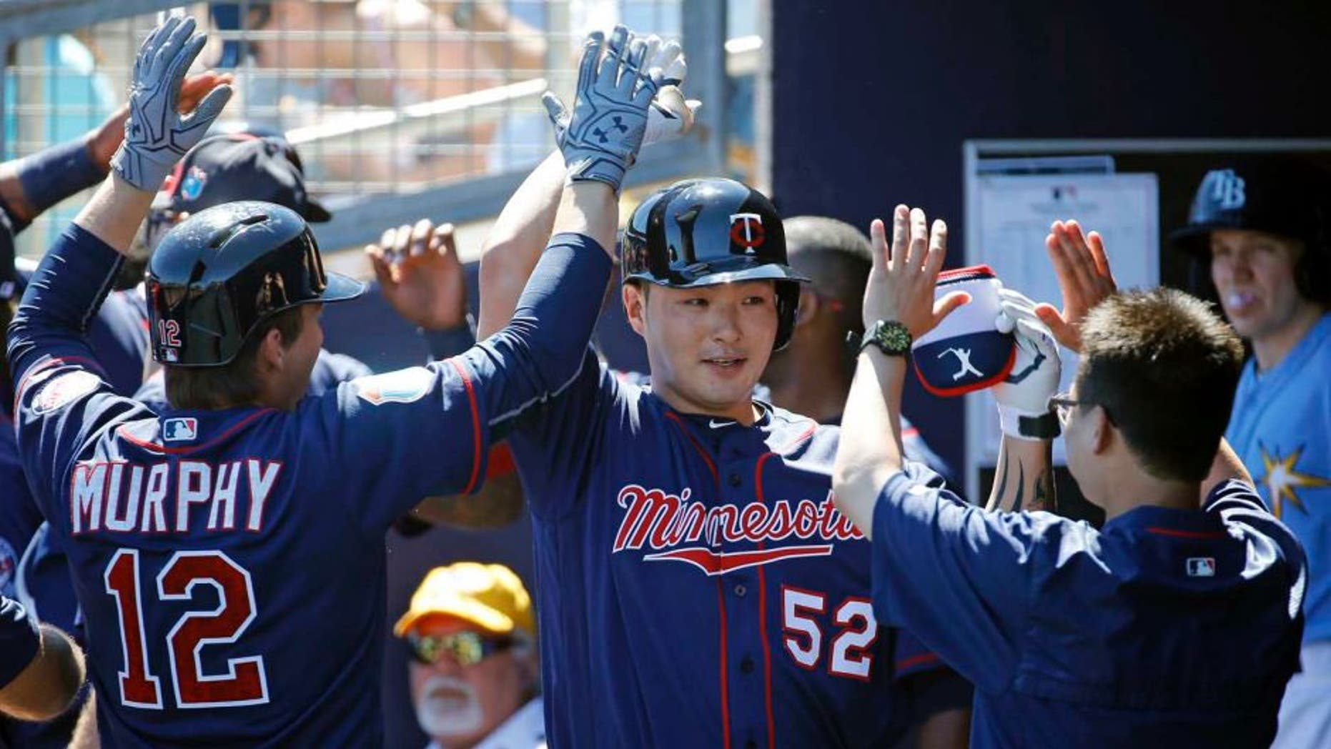 The Minnesota Twins' Byung Ho Park (center) high-fives teammates in the dugout after hitting a grand slam in the first inning of a spring training game against the Tampa Bay Rays in Port Charlotte, Fla., on Sunday, March 6, 2016.