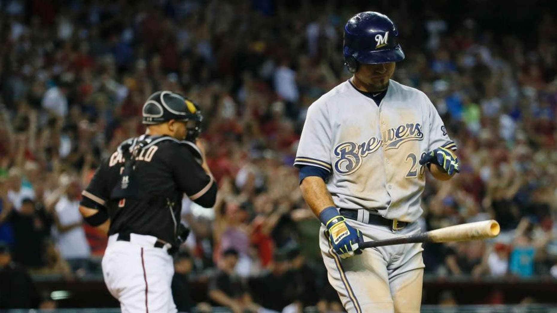 The Milwaukee Brewers' Gerardo Parra walks to the dugout after striking out with the bases loaded to end the game as Arizona Diamondbacks catcher Welington Castillo runs to the mound, Saturday, July 25, 2015, in Phoenix. The Diamondbacks won 2-0.