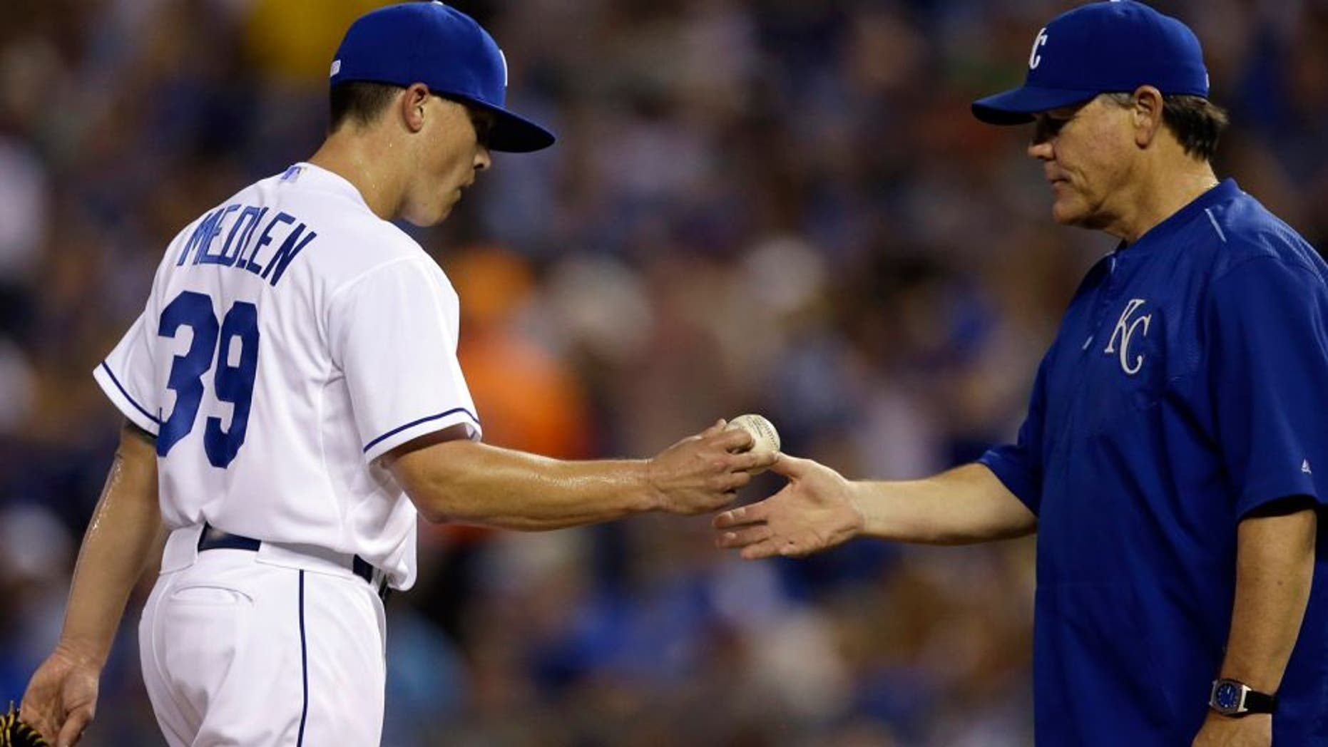 Kansas City Royals starting pitcher Kris Medlen (39) hands the ball to manager Ned Yost, right, during the sixth inning of a baseball game against the Chicago White Sox at Kauffman Stadium in Kansas City, Mo., Friday, Sept. 4, 2015. (AP Photo/Orlin Wagner)