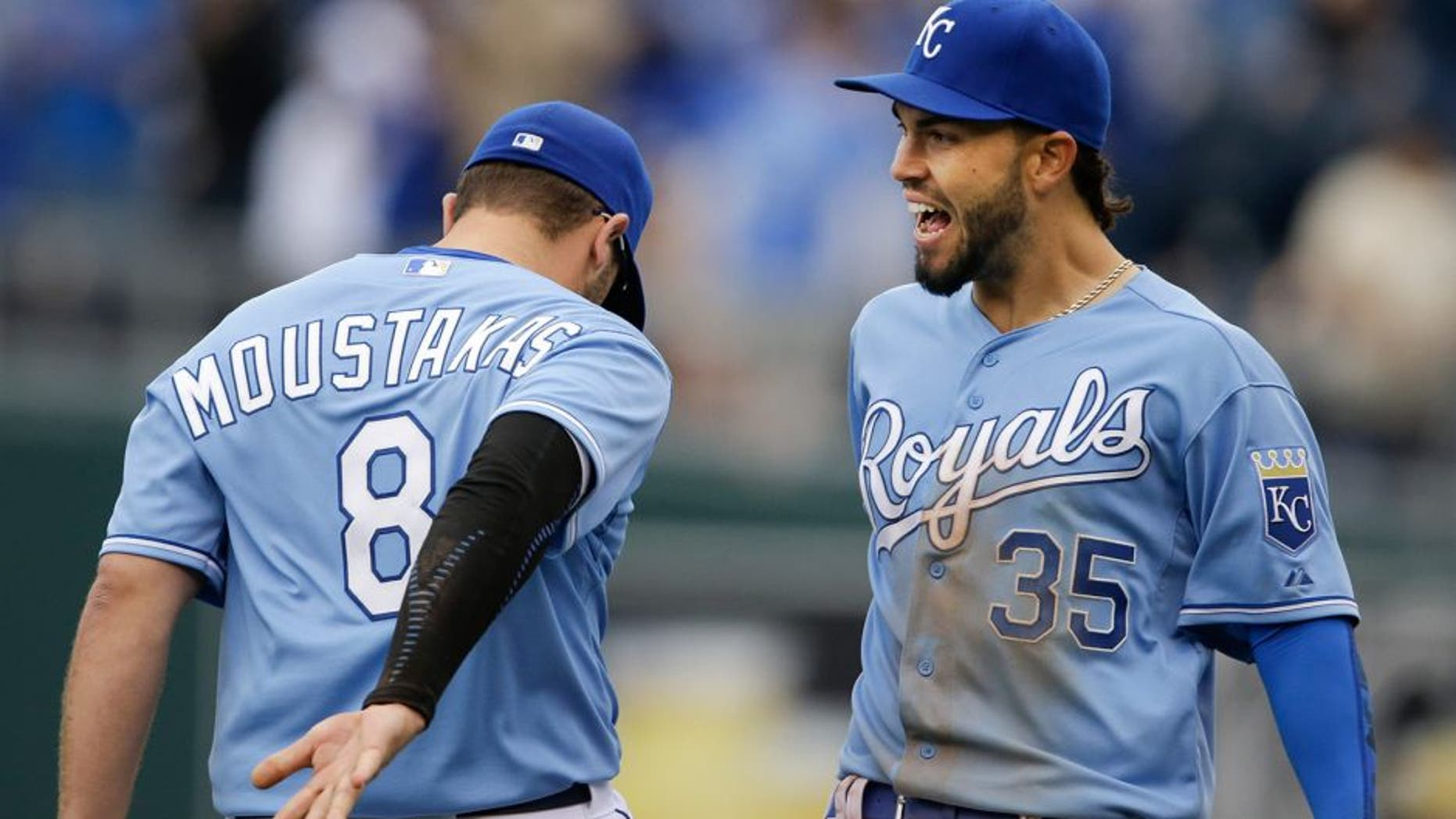 Kansas City Royals first baseman Eric Hosmer (35) and third baseman Mike Moustakas (8) celebrate following a baseball game against the Chicago White Sox at Kauffman Stadium in Kansas City, Mo., Thursday, April 9, 2015. The Royals defeated the White Sox 4-1. (AP Photo/Orlin Wagner)
