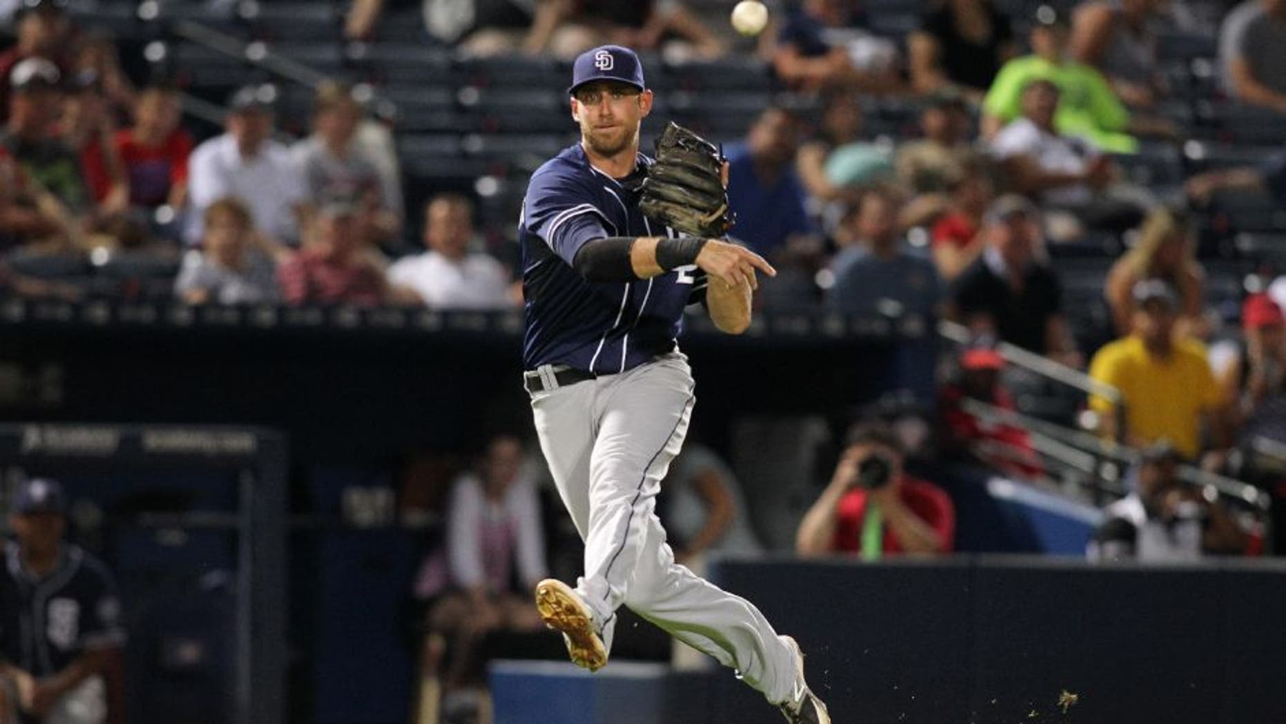 San Diego Padres third baseman Will Middlebrooks (11) throws a runner out at first base against the Atlanta Braves in the tenth inning at Turner Field.