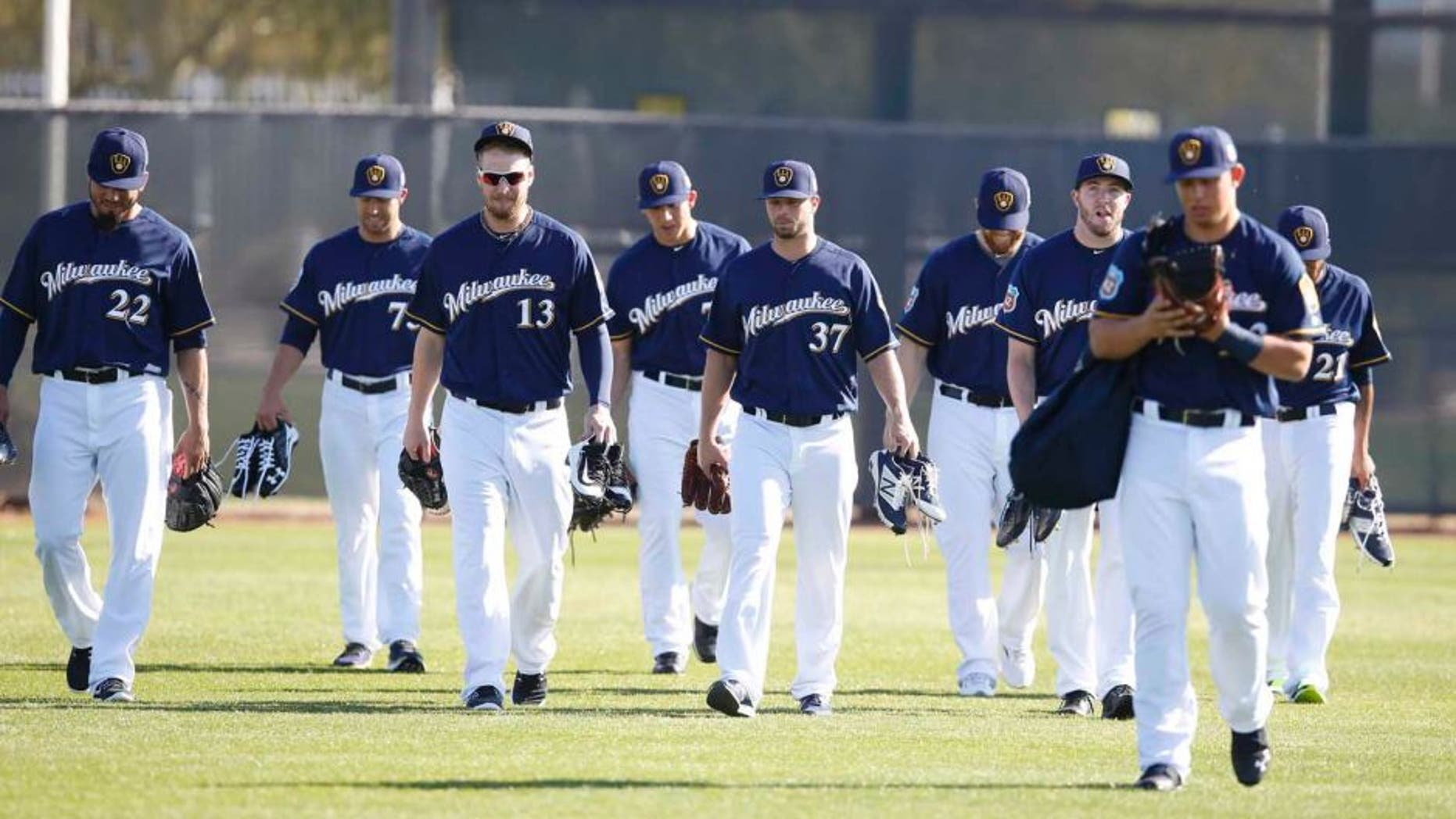 Milwaukee Brewers pitchers and catchers walk on the field during spring training camp at Maryvale Baseball Park in Maryvale, Ariz., on Sunday, Feb. 21, 2016.
