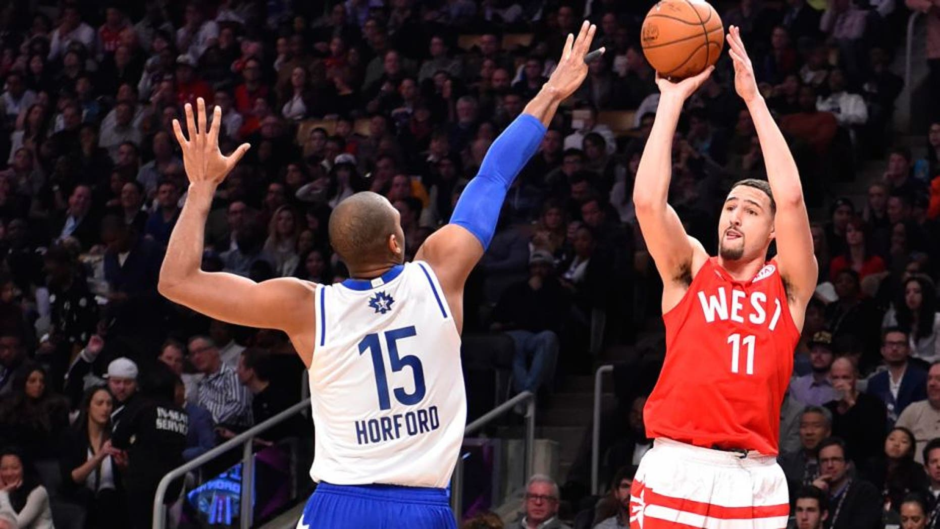Feb 14, 2016; Toronto, Ontario, CAN; Western Conference guard Klay Thompson of the Golden State Warriors (11) shoots against Eastern Conference player Al Horford (15) of the Atlanta Hawks in the first half of the NBA All Star Game at Air Canada Centre. Mandatory Credit: Bob Donnan-USA TODAY Sports