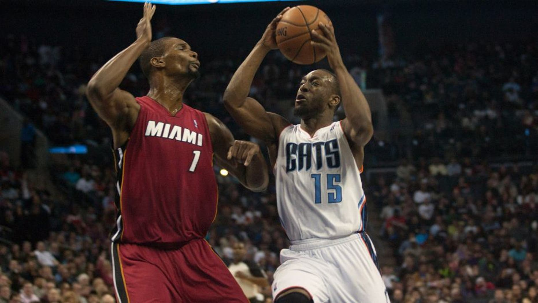 Jan 18, 2014; Charlotte, NC, USA; Charlotte Bobcats point guard Kemba Walker (15) goes up for a shot over Miami Heat center Chris Bosh (1) during the second half at Time Warner Cable Arena. The Heat defeated the Bobcats 104-96 in overtime. Mandatory Credit: Jeremy Brevard-USA TODAY Sports