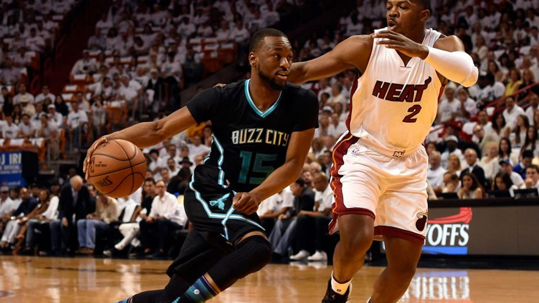 May 1, 2016; Miami, FL, USA; Charlotte Hornets guard Kemba Walker (15) drives to the basket as Miami Heat forward Joe Johnson (2) defends during the first half in game seven of the first round of the NBA Playoffs at American Airlines Arena. Mandatory Credit: Steve Mitchell-USA TODAY Sports
