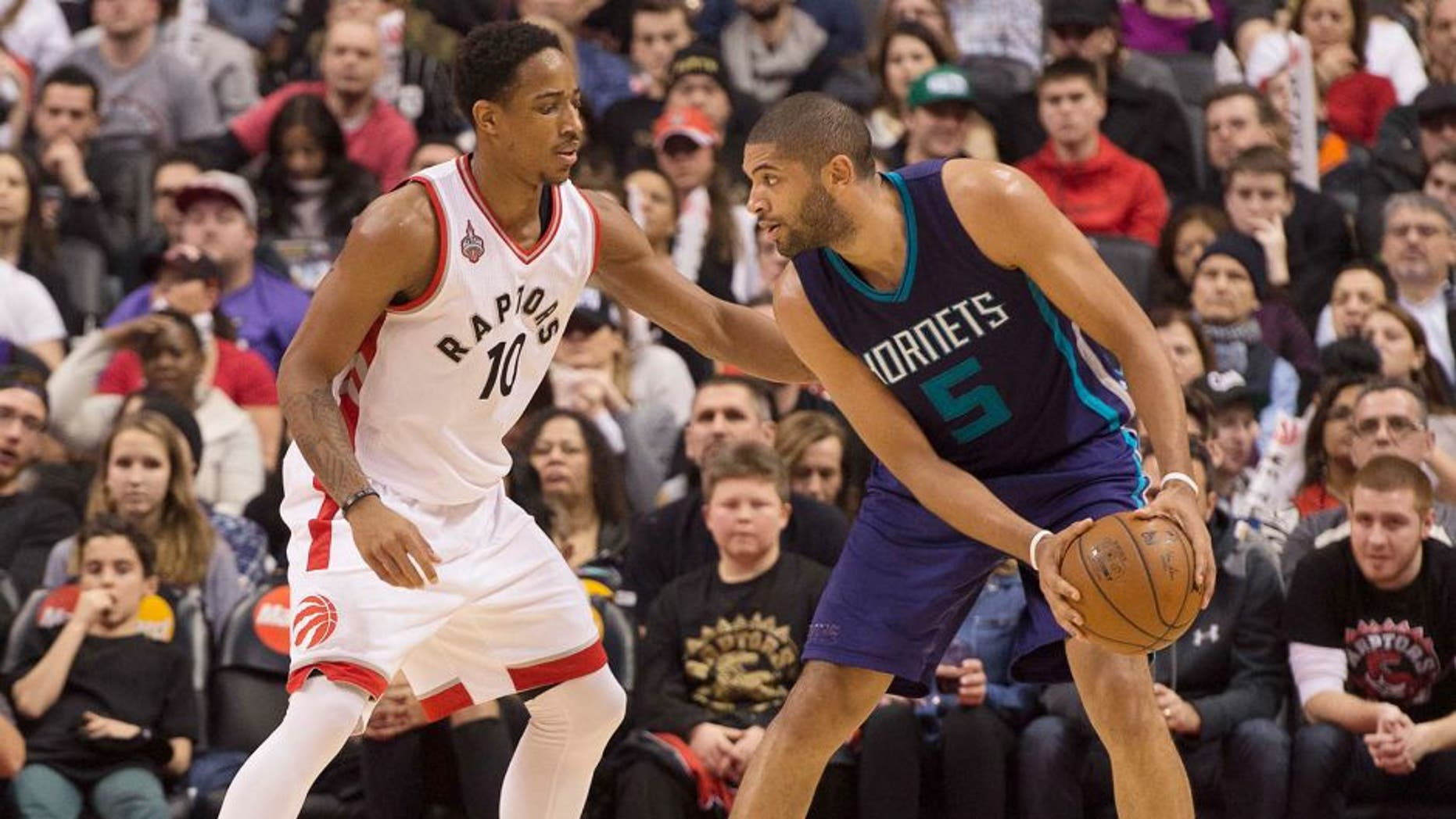 Jan 1, 2016; Toronto, Ontario, CAN;Charlotte Hornets guard Nicolas Batum (5) looks to play a ball as Toronto Raptors guard DeMar DeRozan (10) tries to defend during the third quarter in a game at Air Canada Centre. The Toronto Raptors won 104-94. Mandatory Credit: Nick Turchiaro-USA TODAY Sports