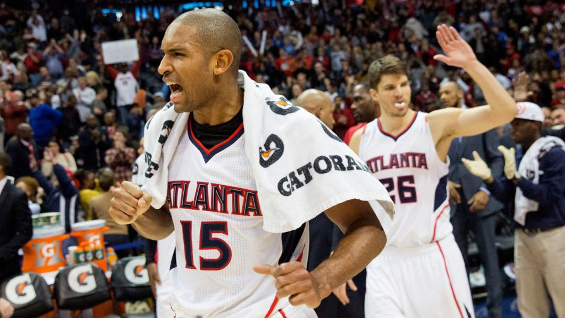 Atlanta Hawks' Al Horford, left, celebrates along with teammate Kyle Korver, right, after they defeated the Oklahoma City Thunder 103-93 to set a franchise record for most consecutive wins at 15 in an NBA basketball game, Friday, Jan. 23, 2015, in Atlanta. (AP Photo/David Goldman)