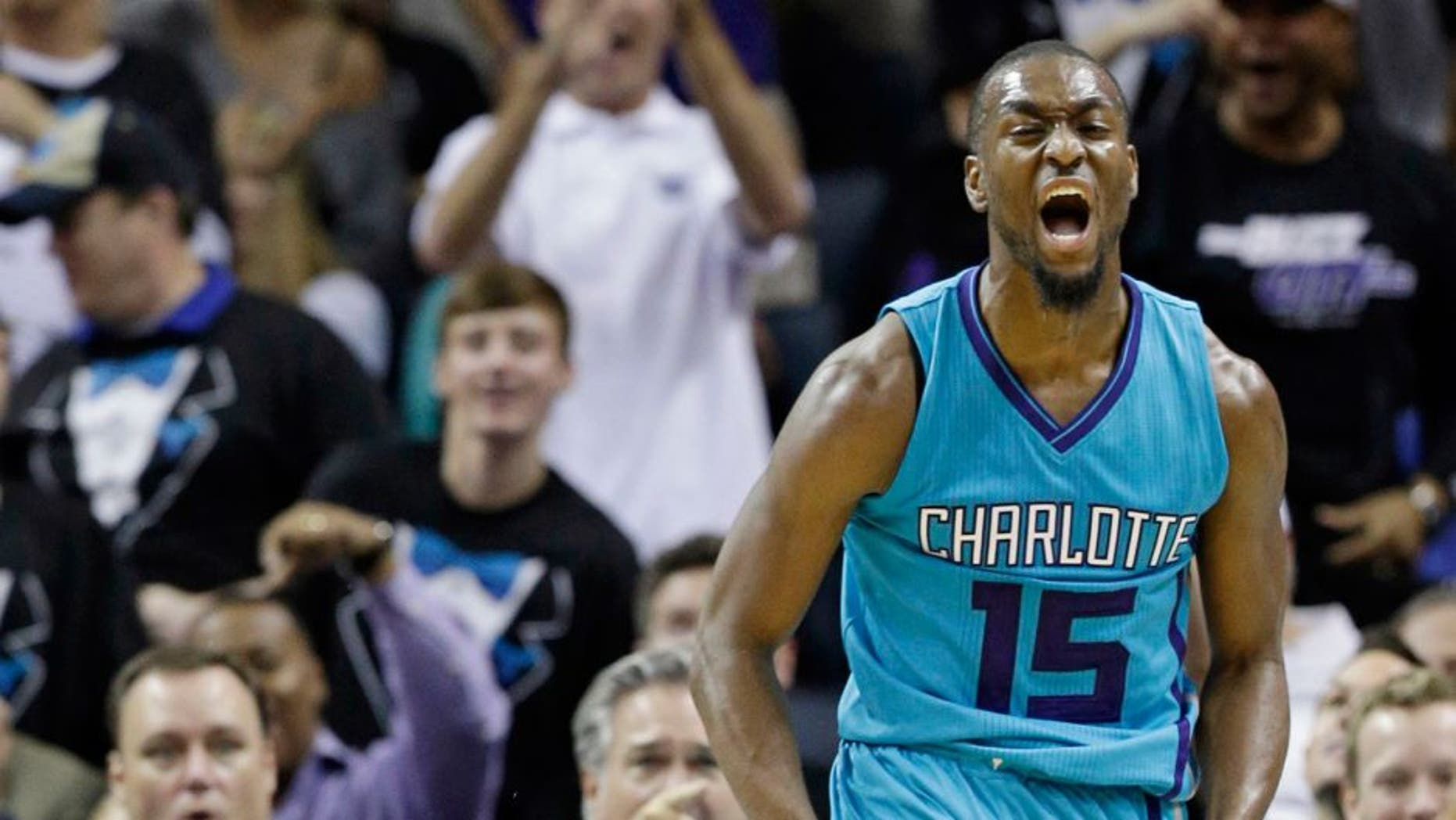 Charlotte Hornets' Kemba Walker (15) reacts after making a basket against the Milwaukee Bucks during the second half of an NBA basketball game in Charlotte, N.C., Wednesday, Oct. 29, 2014. The Hornets won 108-106 in overtime. (AP Photo/Chuck Burton)