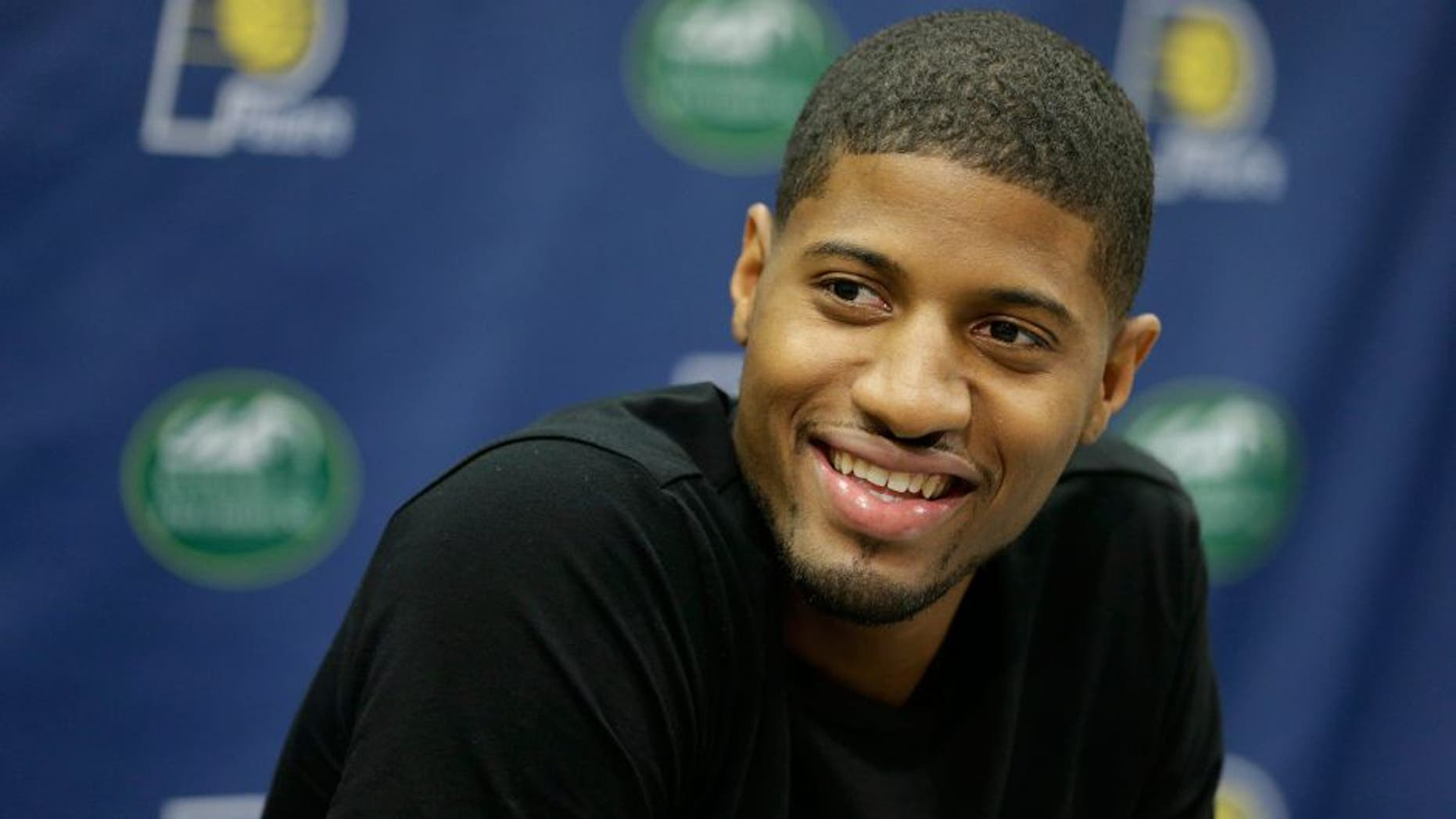 """Indiana Pacers' Paul George responds to a question during a news conference Friday, Aug. 15, 2014, in Indianapolis. George hopes to make it back on the court next season despite the """"freak accident"""" that caused a compound fracture in his right leg. (AP Photo/Darron Cummings)"""