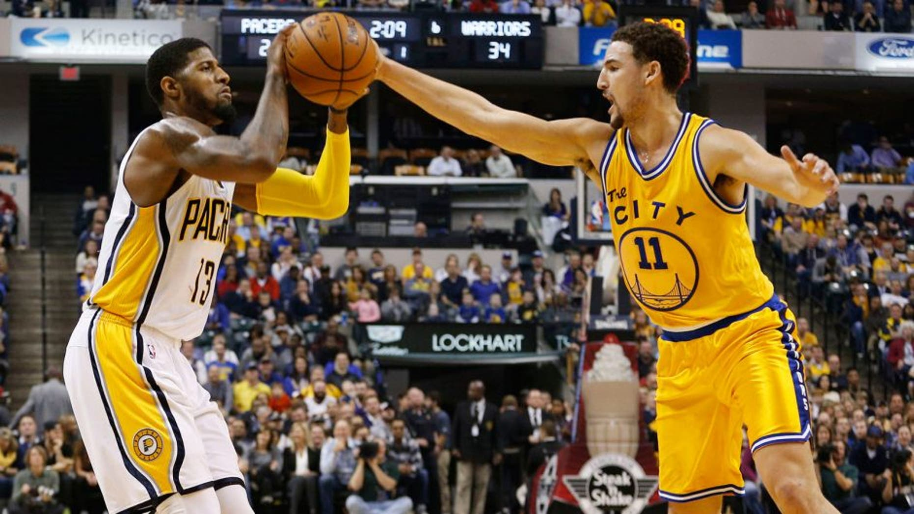 Dec 8, 2015; Indianapolis, IN, USA; Indiana Pacers forward Paul George (13) is guarded by Golden State Warriors guard Klay Thompson (1) at Bankers Life Fieldhouse. Mandatory Credit: Brian Spurlock-USA TODAY Sports